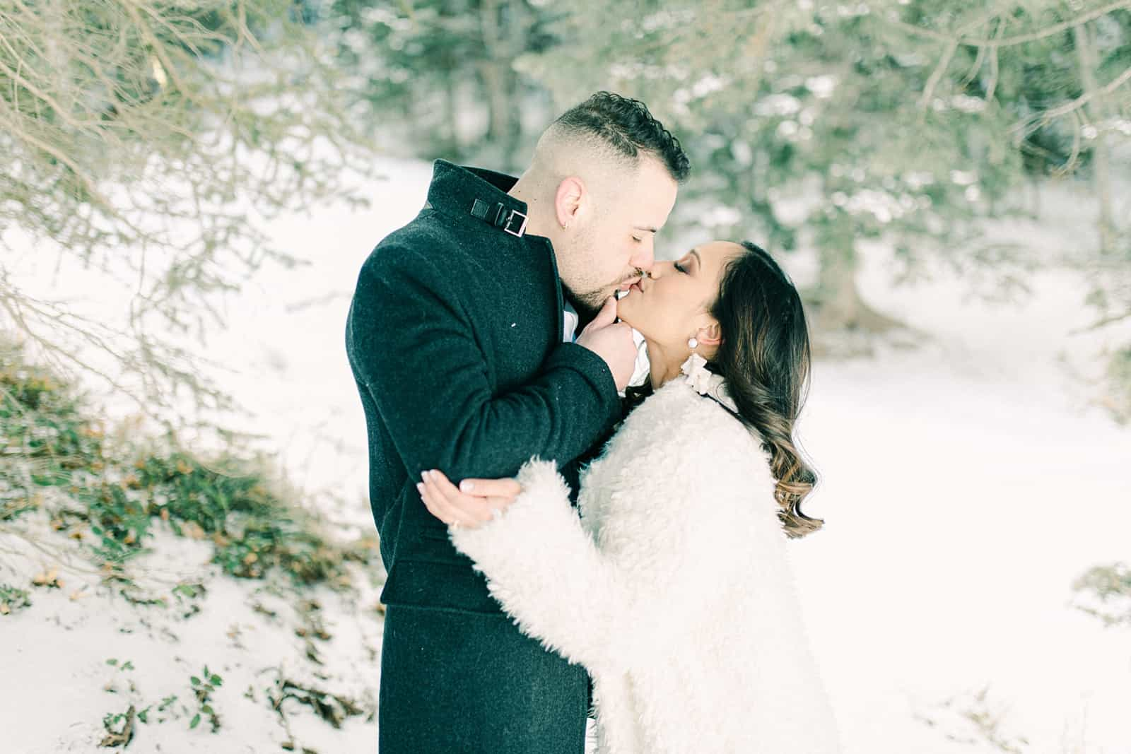 Bride and groom kiss in the winter woods