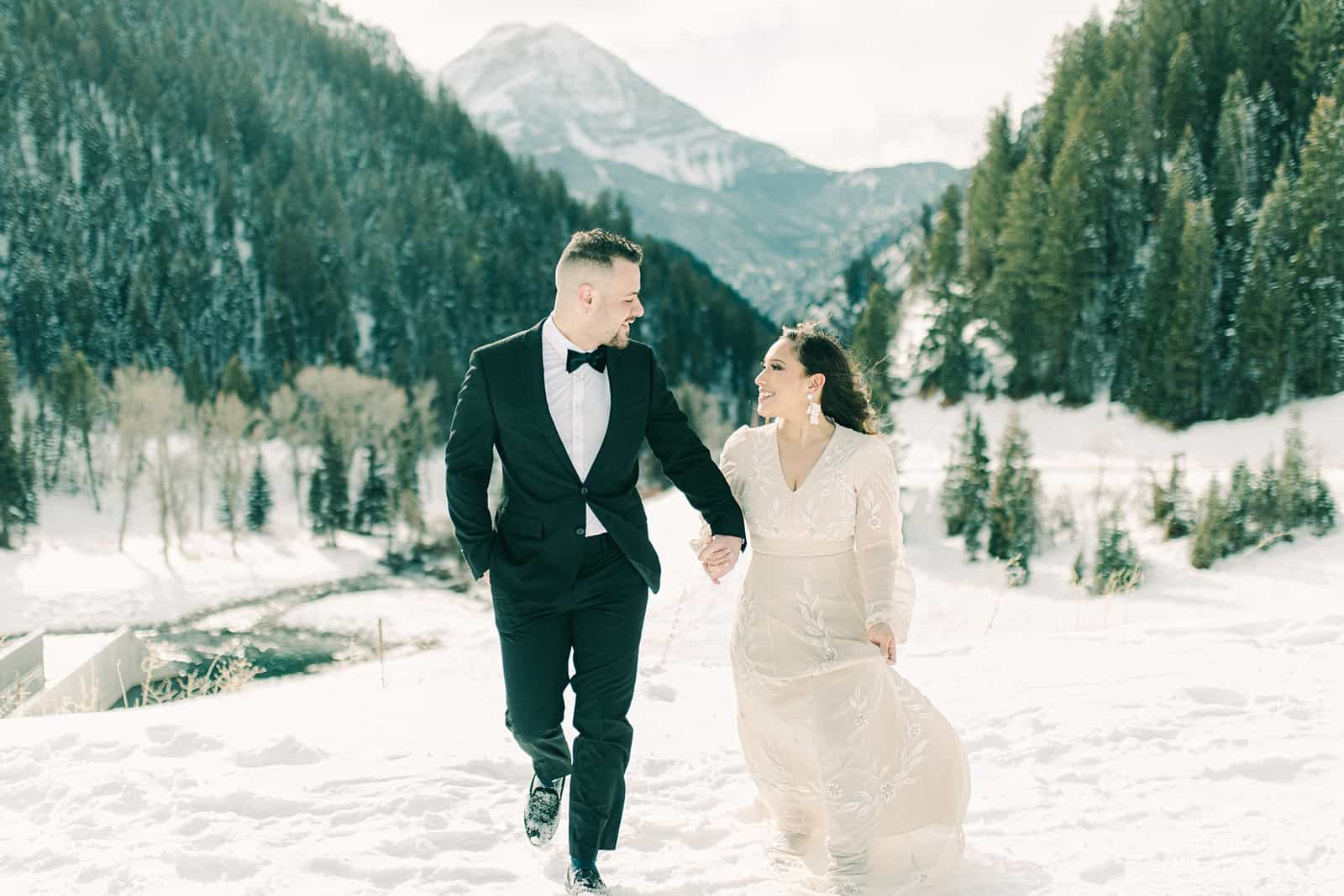 bride and groom walking on winter mountain