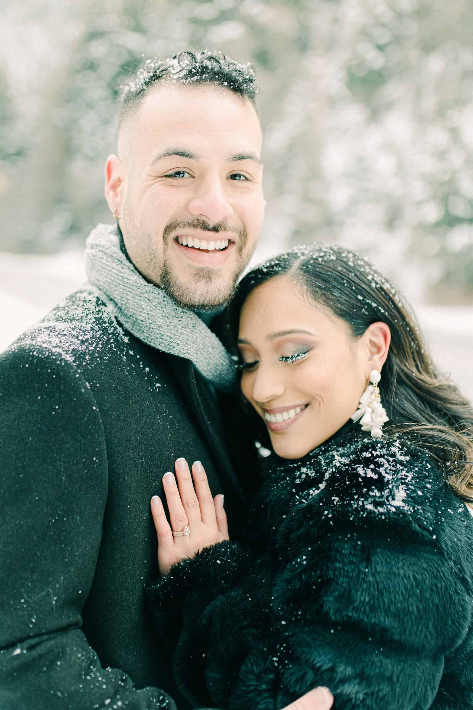 Smiling in the snow, gray scarf and black faux fur coat, engagement ring