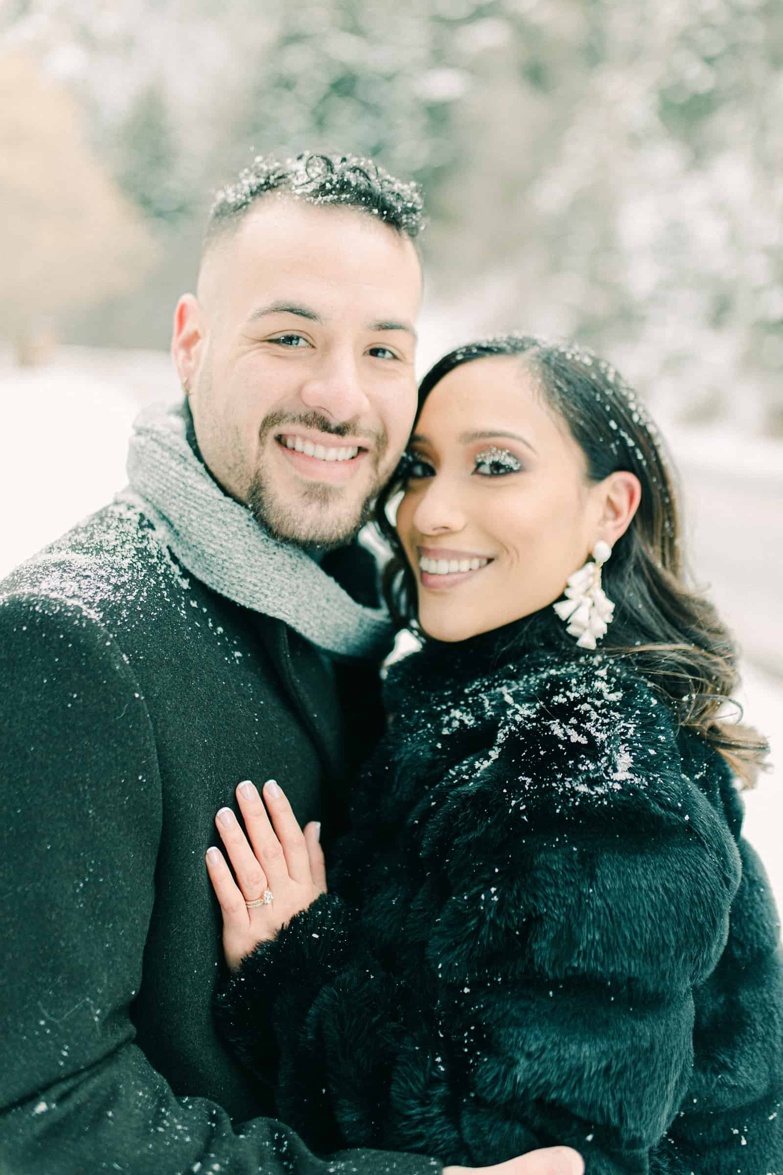 Couple smiling in snowy winter engagement session, snow on eyelashes