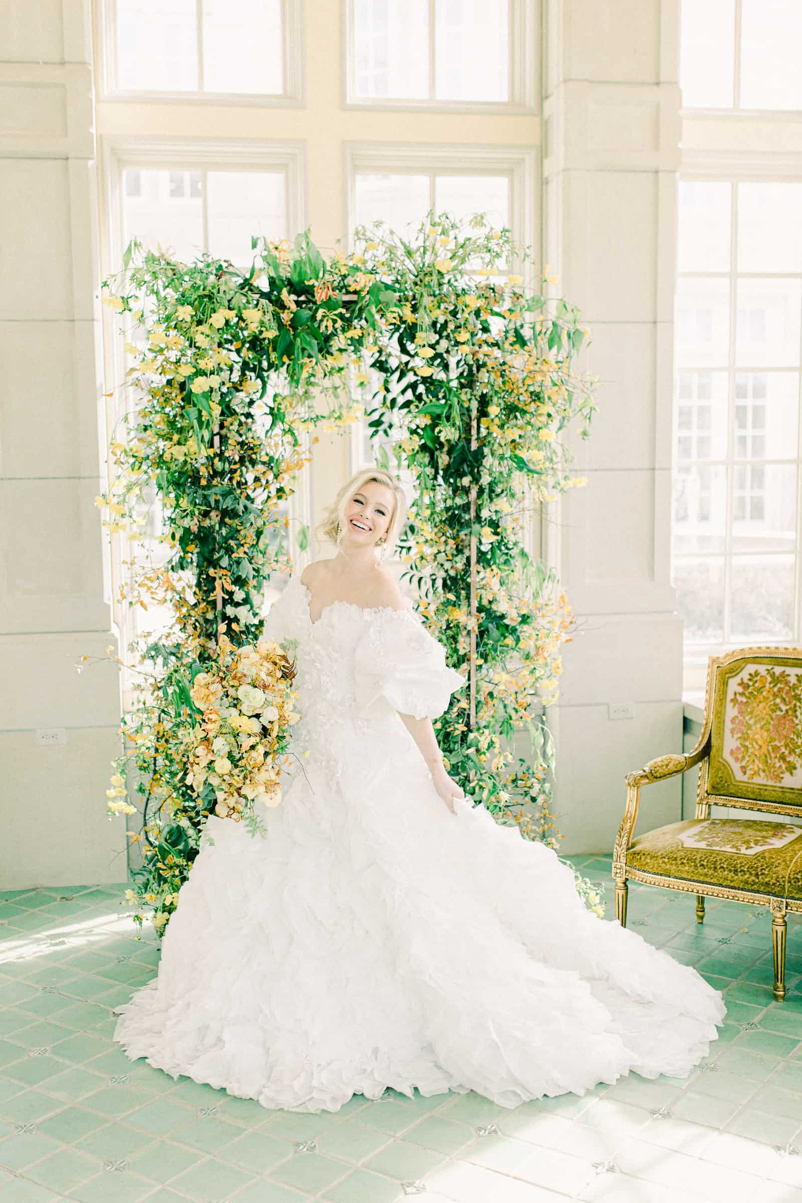 Bride wearing off shoulder ball gown with puff sleeves in front of floral arch