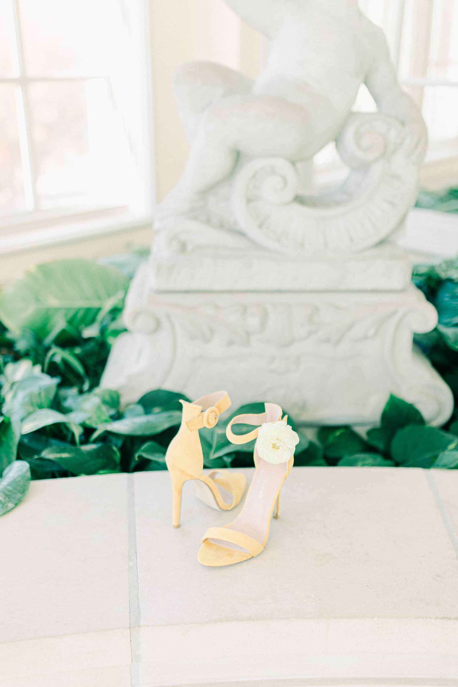 Bride wedding shoes with flowers in greenhouse wedding