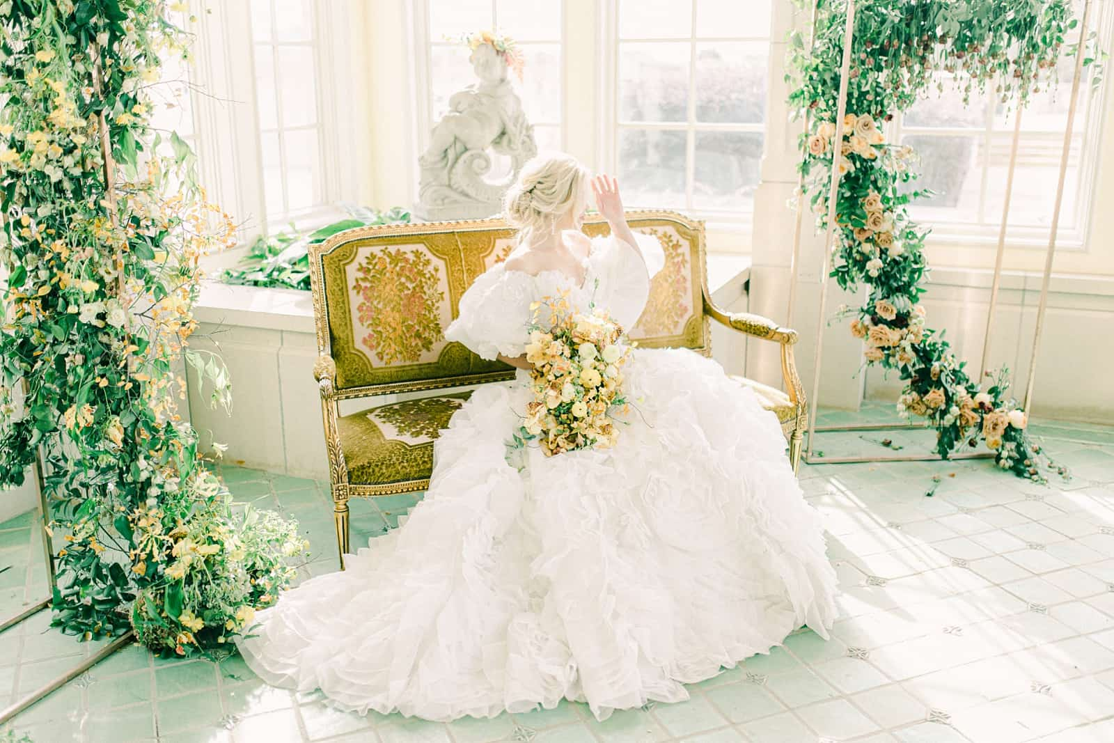 Bride in ball gown sitting on French inspired bench on wedding day