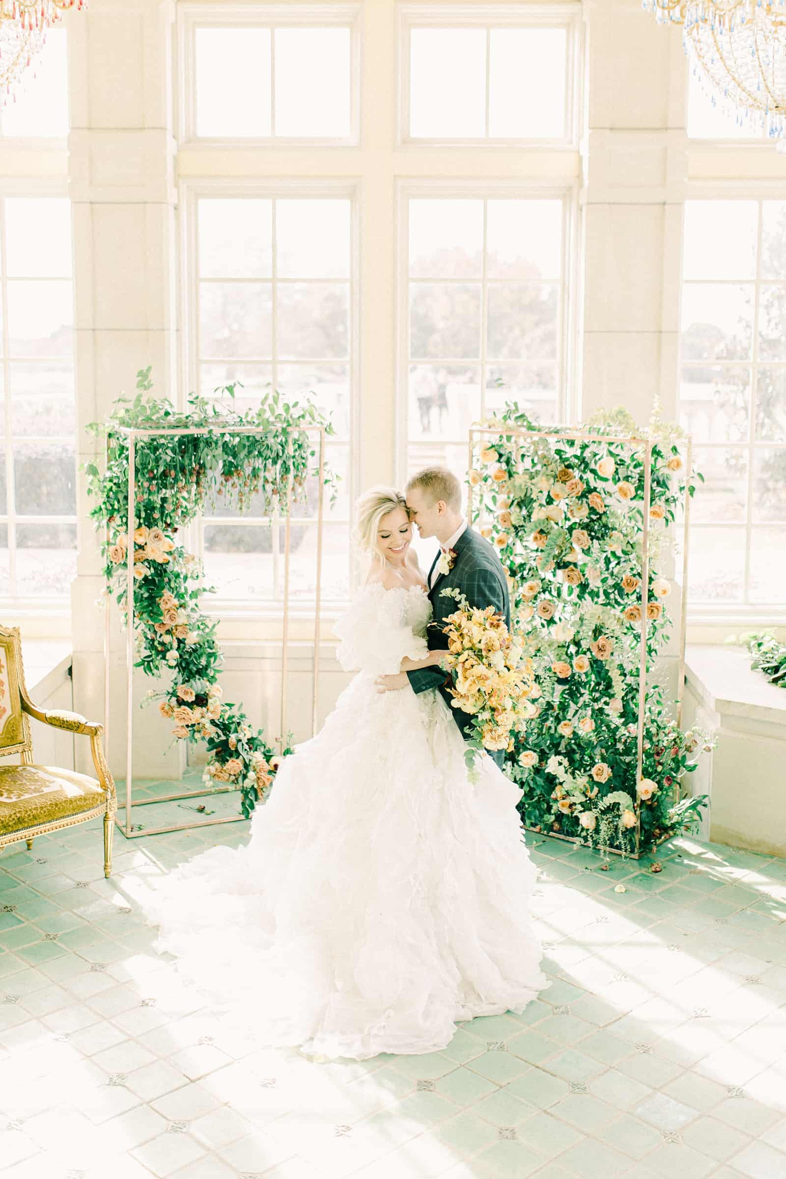 Bride and groom during wedding ceremony surrounded by flower backdrop, destination wedding photography