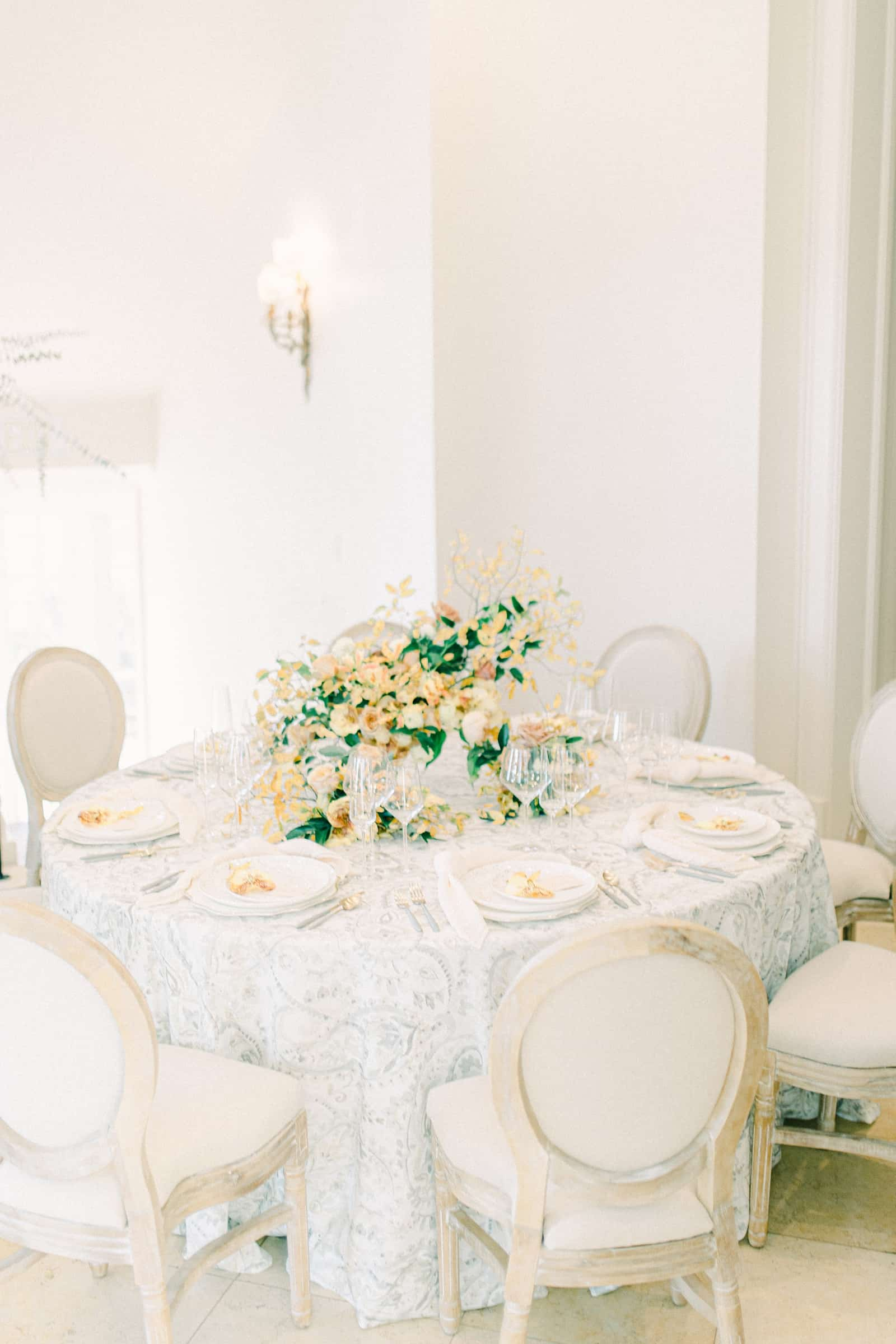 Fine Art wedding table setting with gray damask tablecloth and orange, white and green centerpiece