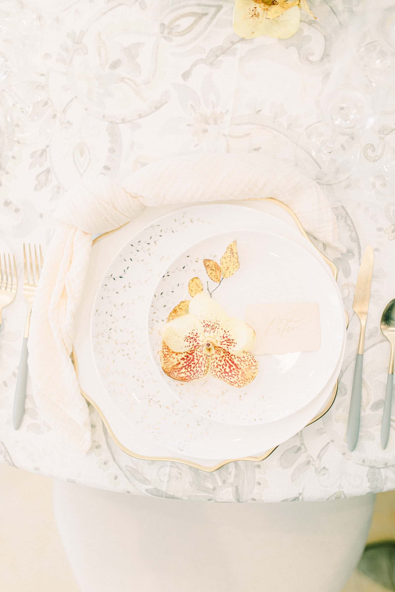 Fine art wedding table place setting with gray watercolor table cloth and orange orchid