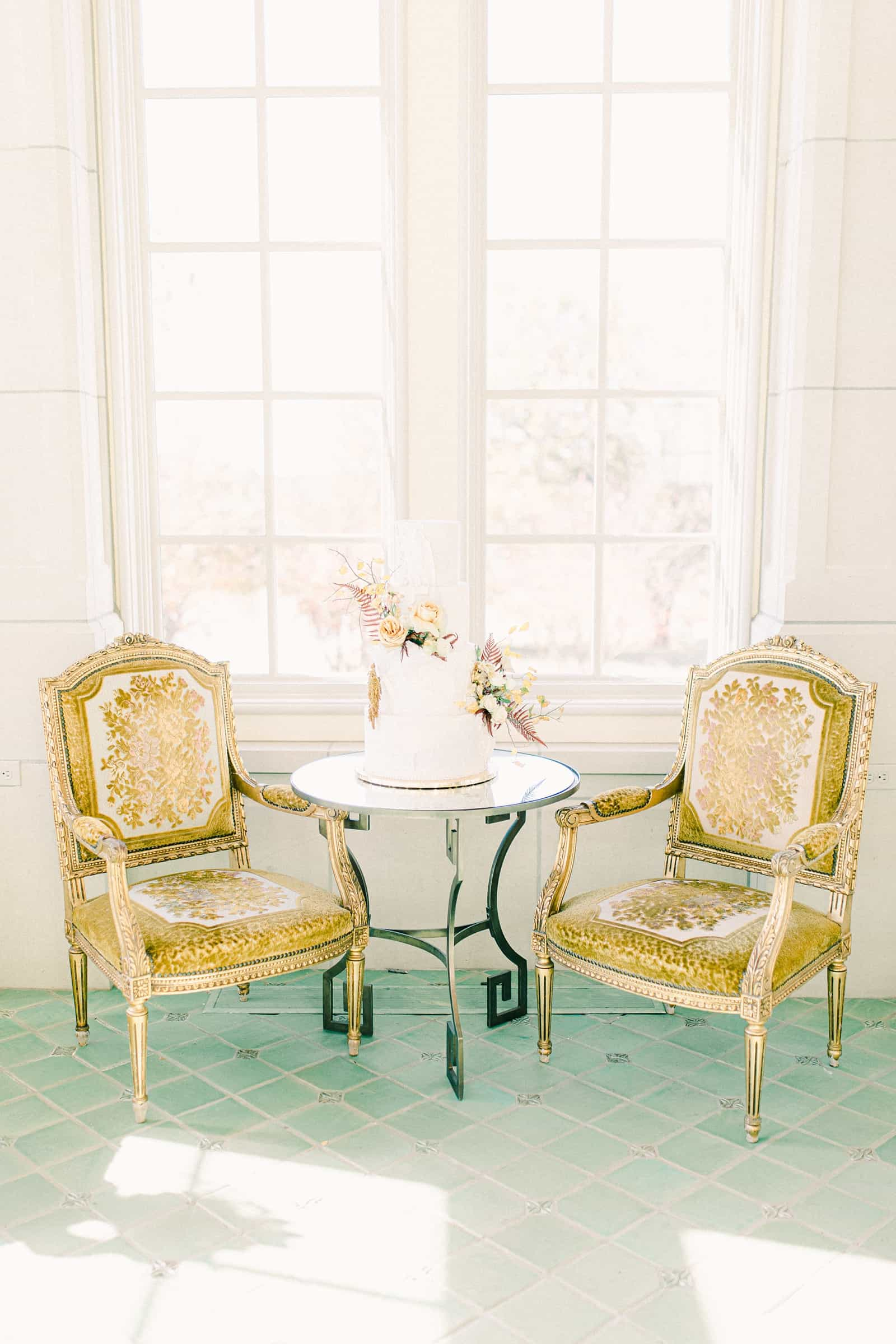 French inspired gold chairs with white, four tiered boho wedding cake