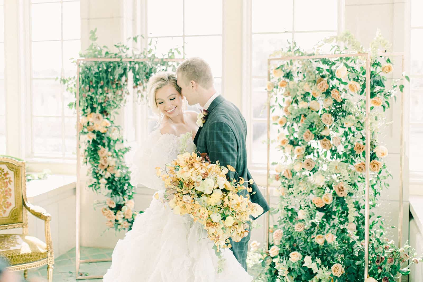 Bride and groom wedding ceremony with elaborate floral backdrop