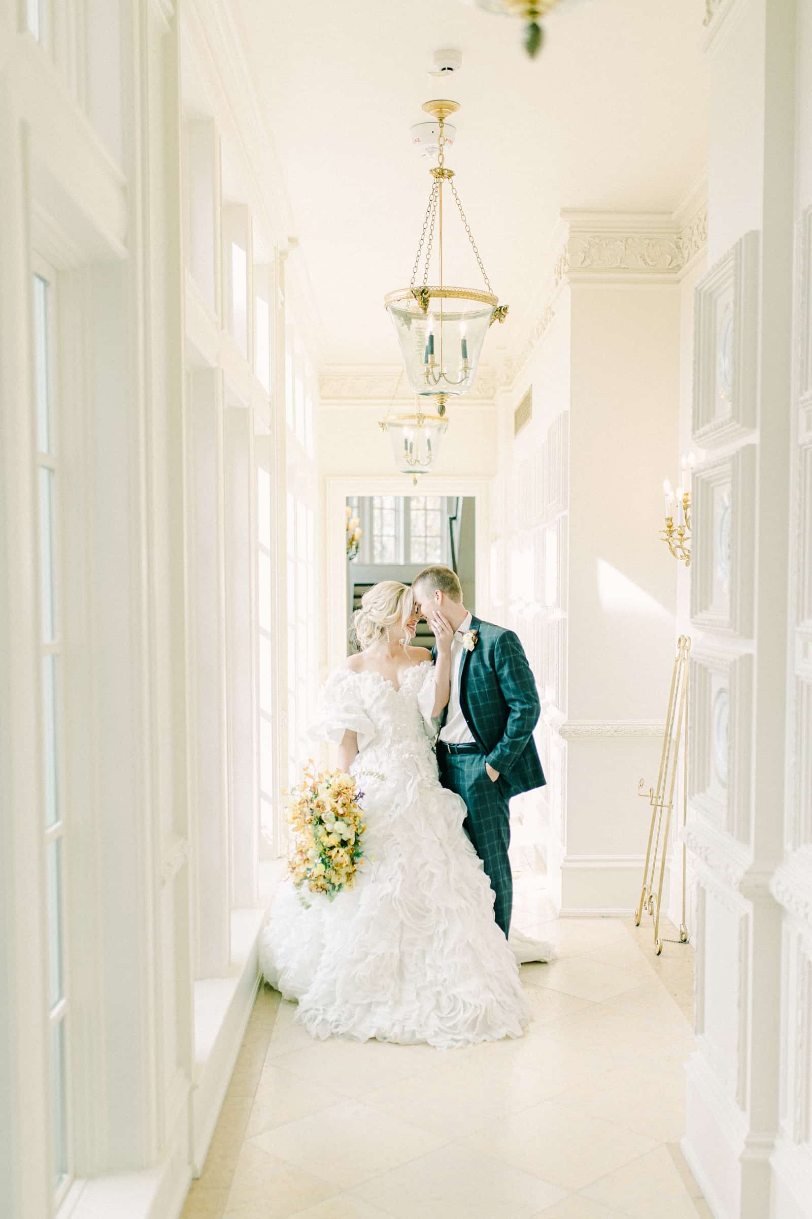 Bride and groom smile in white hallway at European destination wedding venue