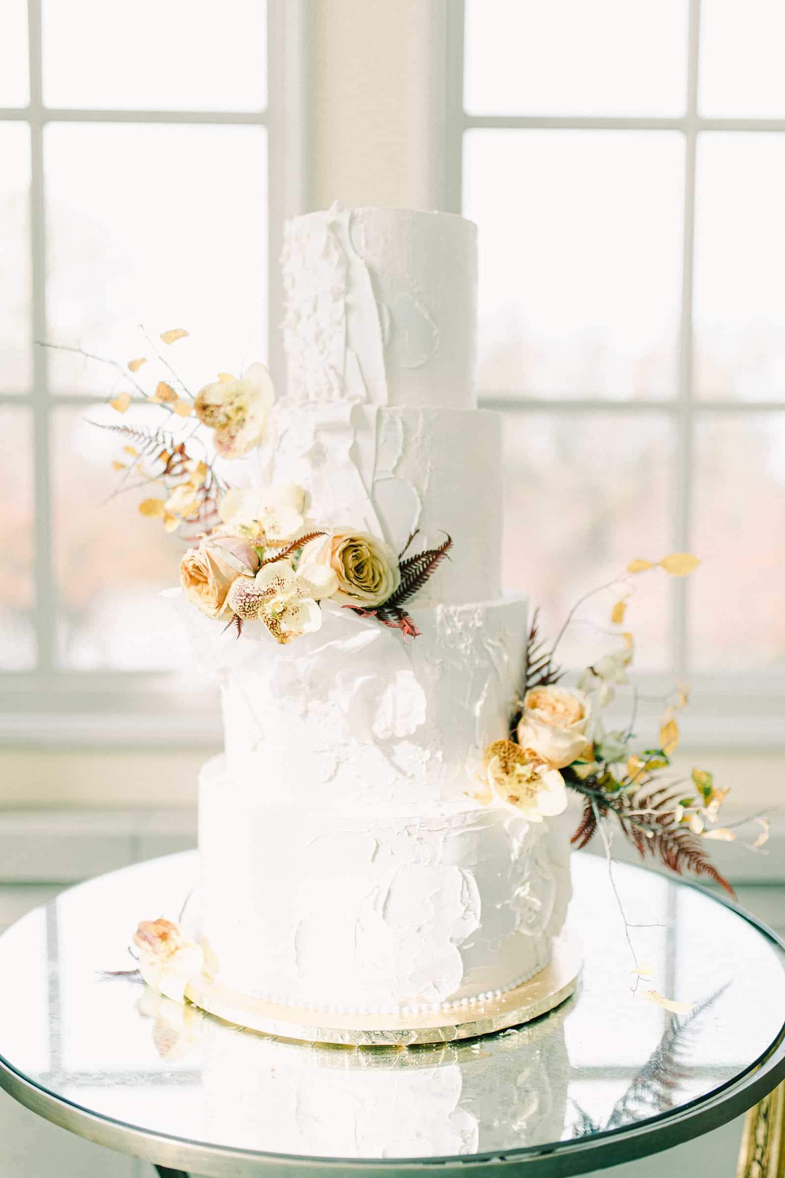 White textured fall wedding cake with four tiers and orange and brown wedding flowers