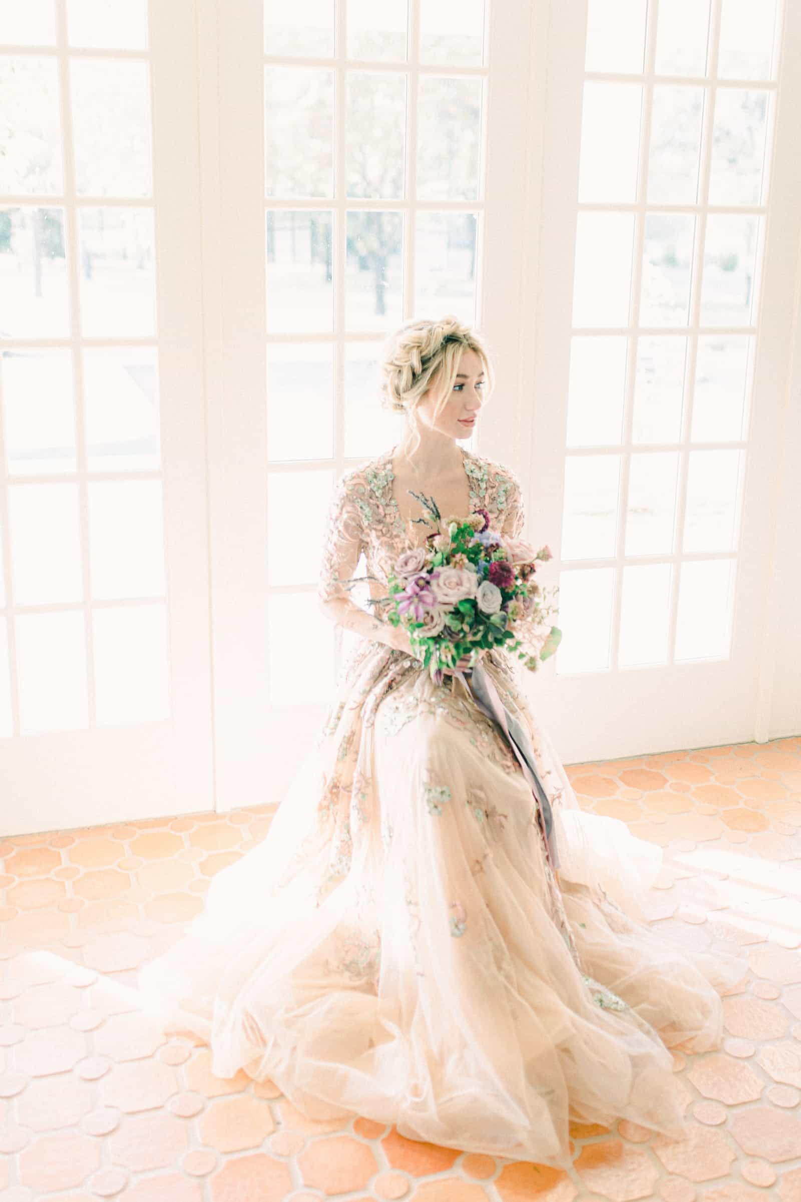 Boho bride in front of large windows with purple flower bouquet