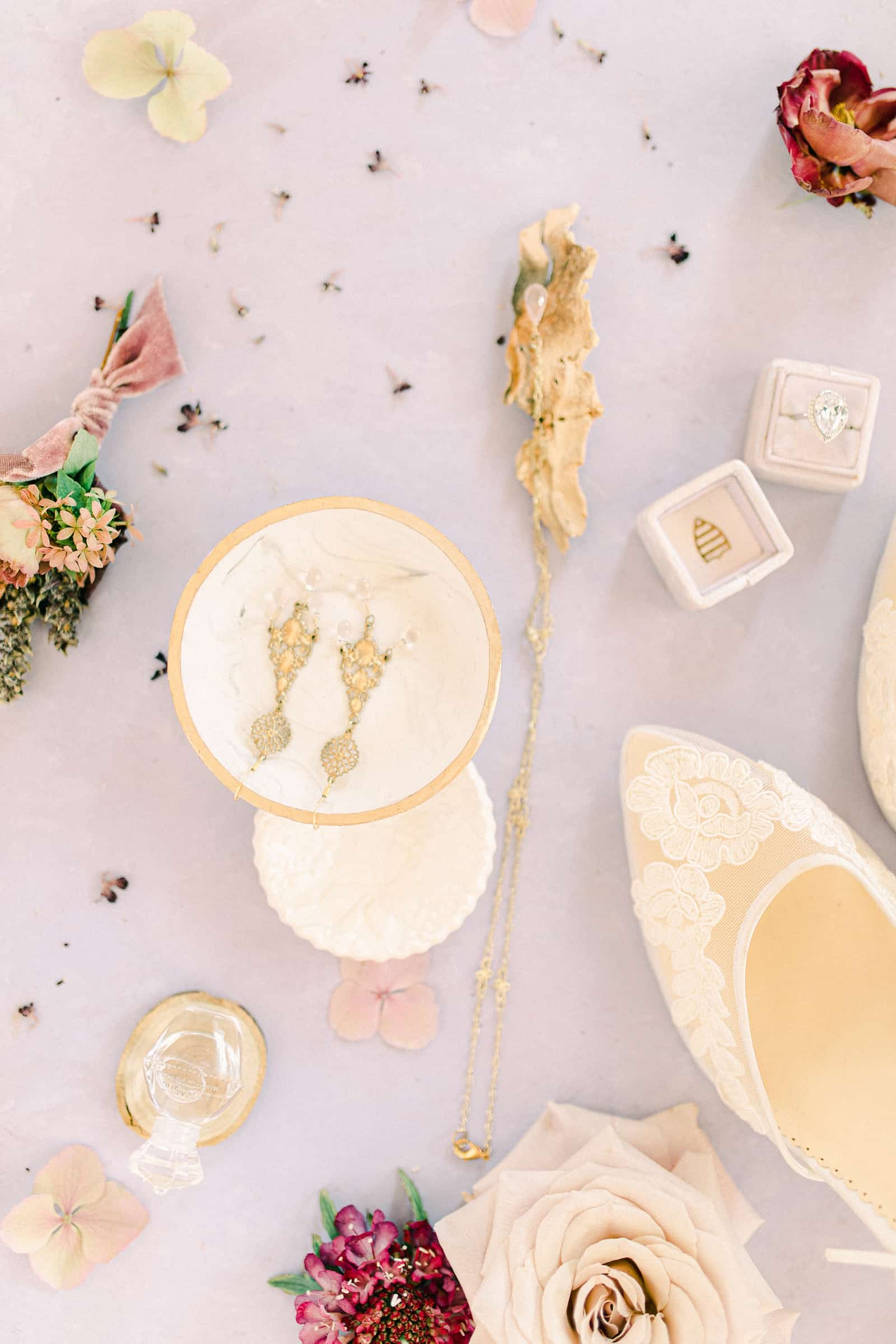 Fine art wedding details flat lay with purple tablecloth and designer shoes for the bride, gold wedding earrings
