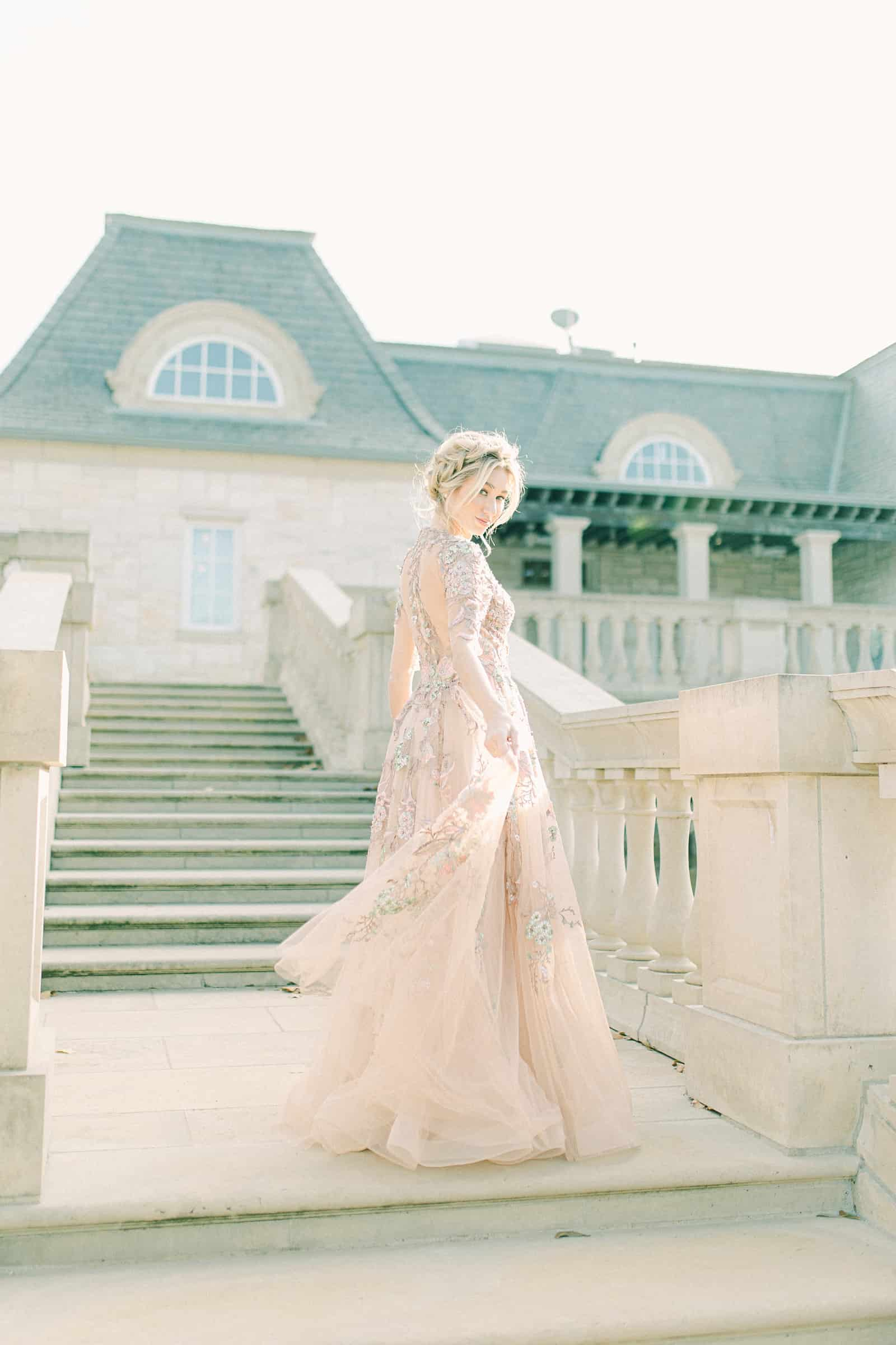 Bride walking down staircase wearing YSA Makino couture wedding dress with floral embellishments and embroidery, flowy wedding dress