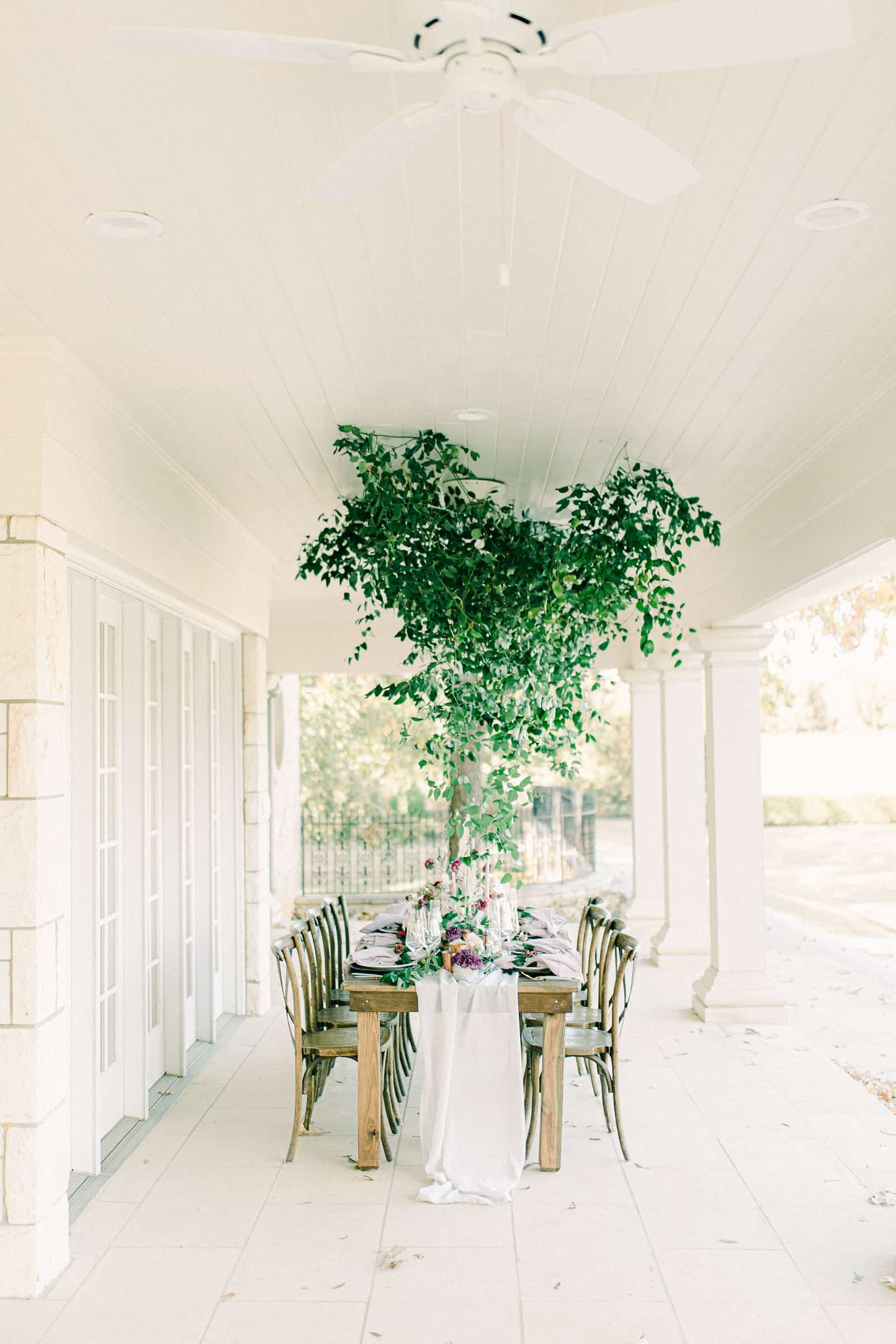 Wedding reception table for bridal party with canopy of greenery on ceiling