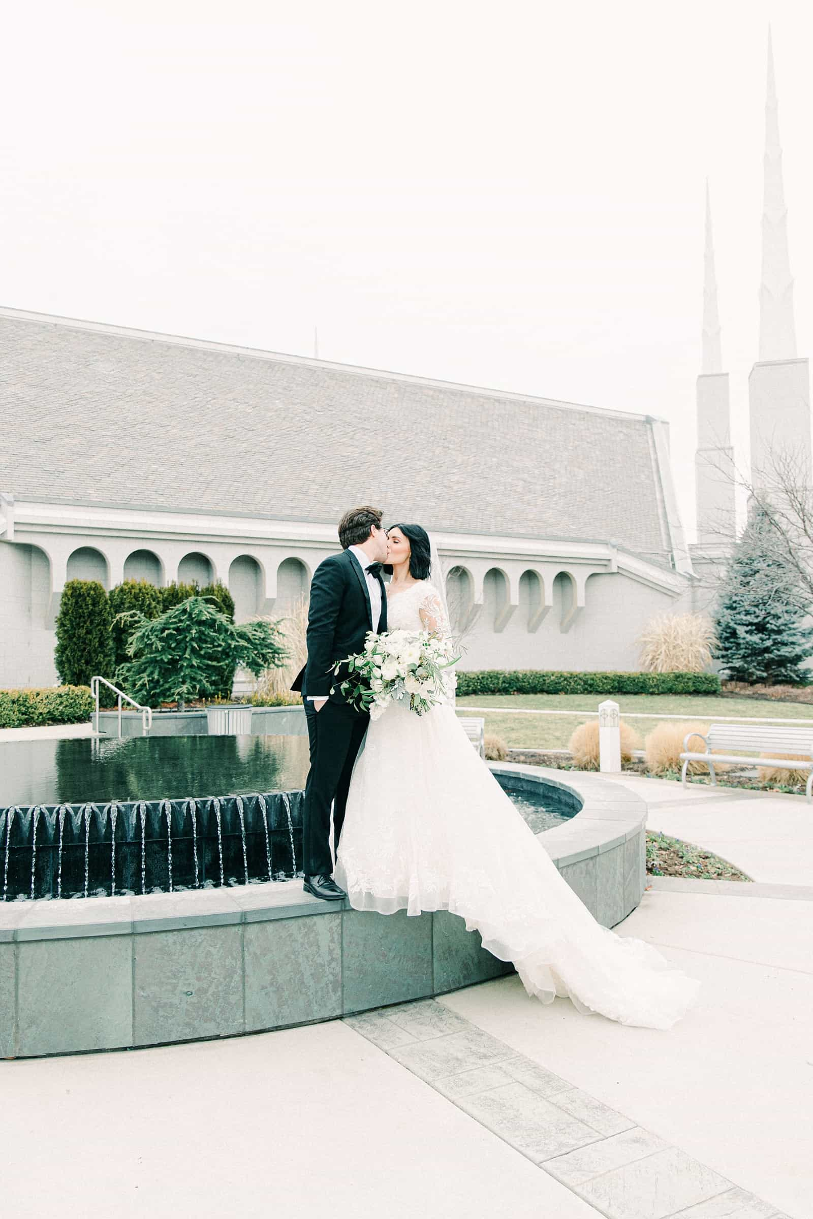 Boise LDS Temple wedding, bride and groom kiss in front of fountain winter wedding