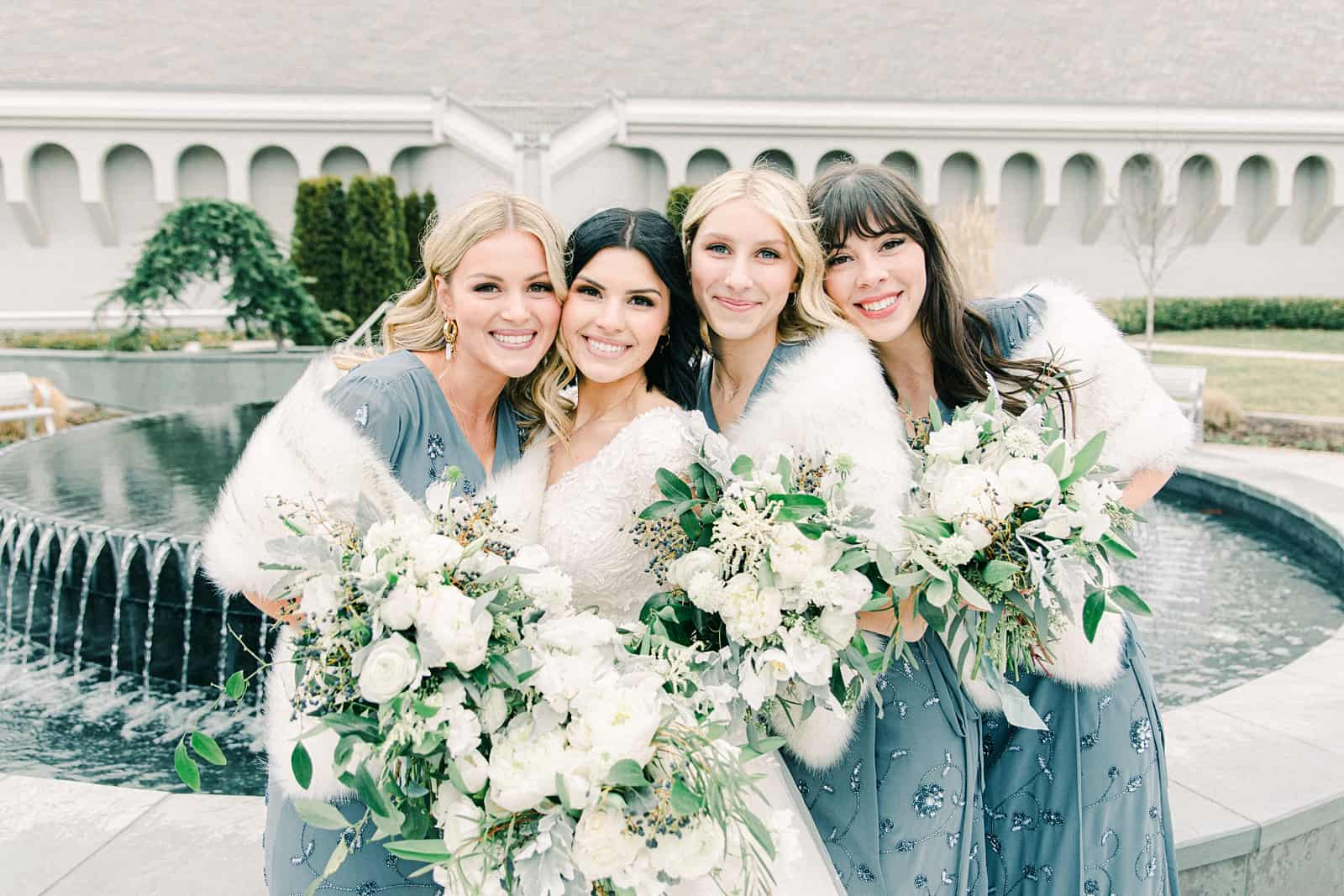 Winter wedding bride with bridesmaids, blue beaded bridesmaids dresses with white fur stoles