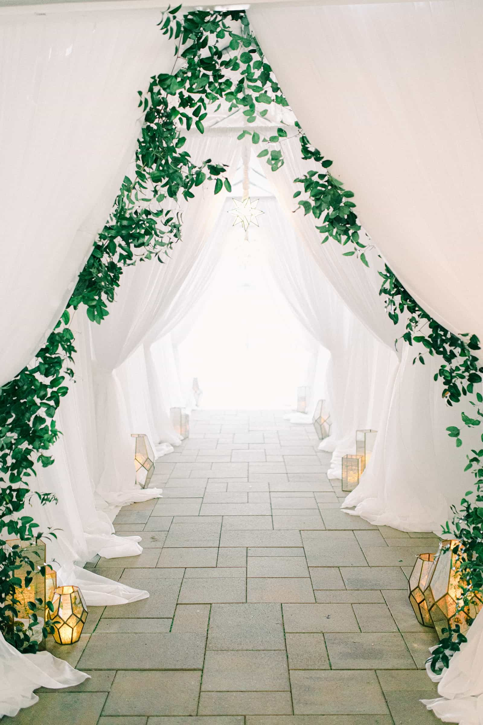 Luxury winter wedding at Willowbridge Estate in Boise, Idaho, white tent reception entrance with greenery and candles lanterns