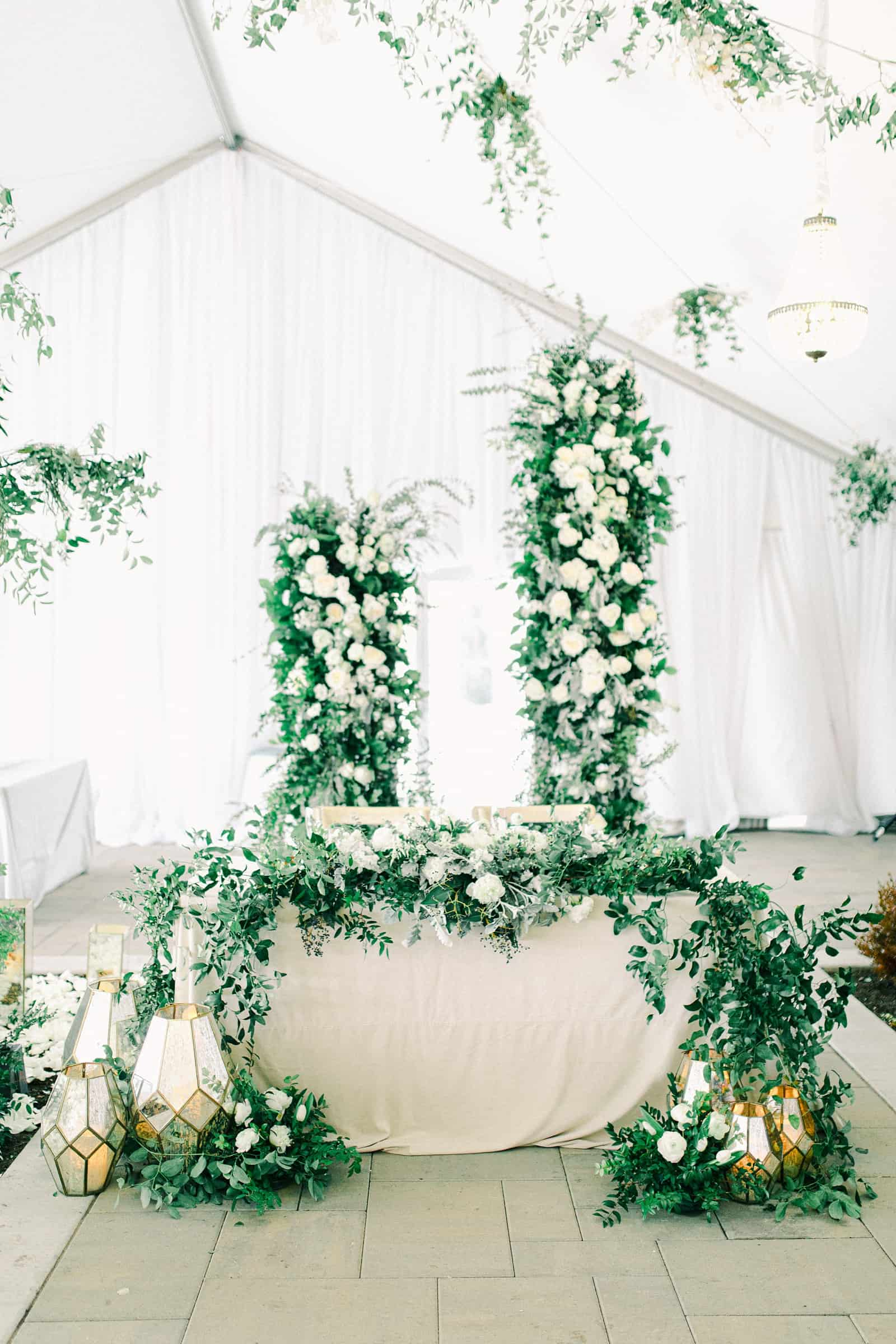 Luxury winter wedding at Willowbridge Estate in Boise, Idaho, floral arch with white flowers roses and greenery backdrop