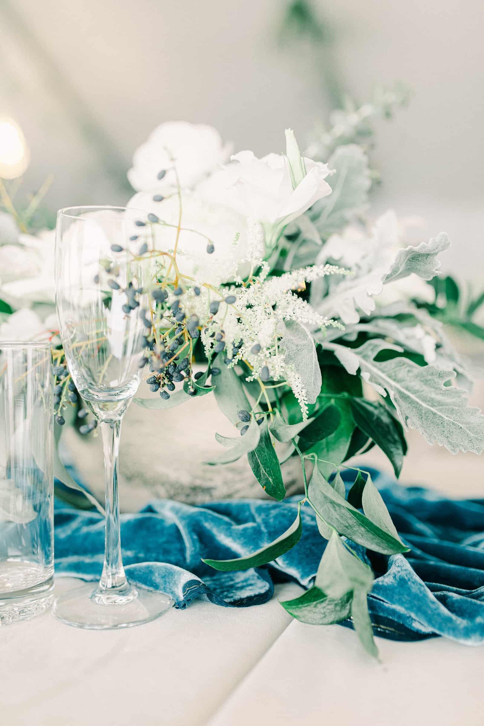 Winter wedding at Willowbridge Estate in Boise, Idaho, all white rose centerpieces with blue velvet runner
