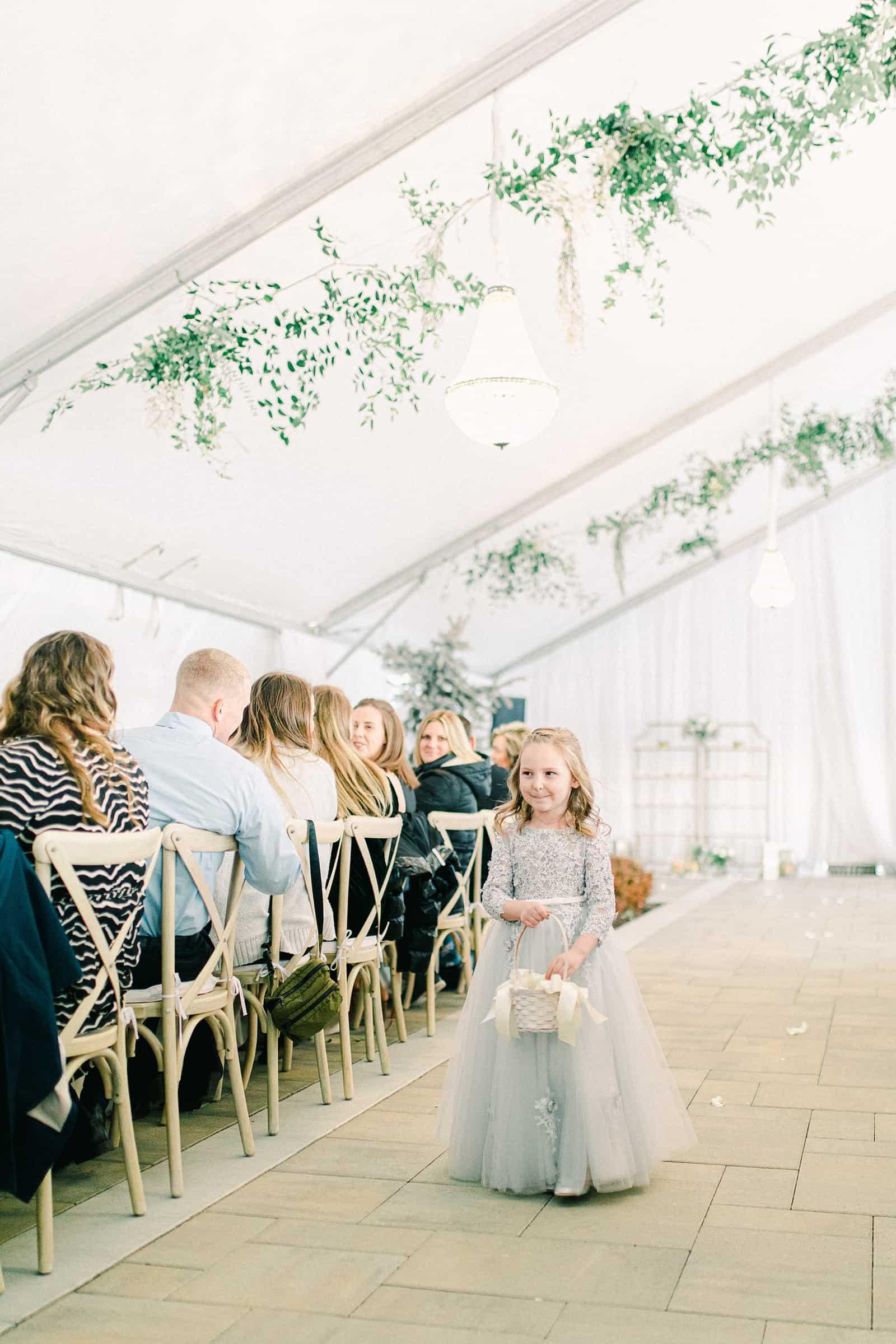 Luxury winter wedding at Willowbridge Estate in Boise, Idaho, little flower girl walks down aisle in blue flower girl dress