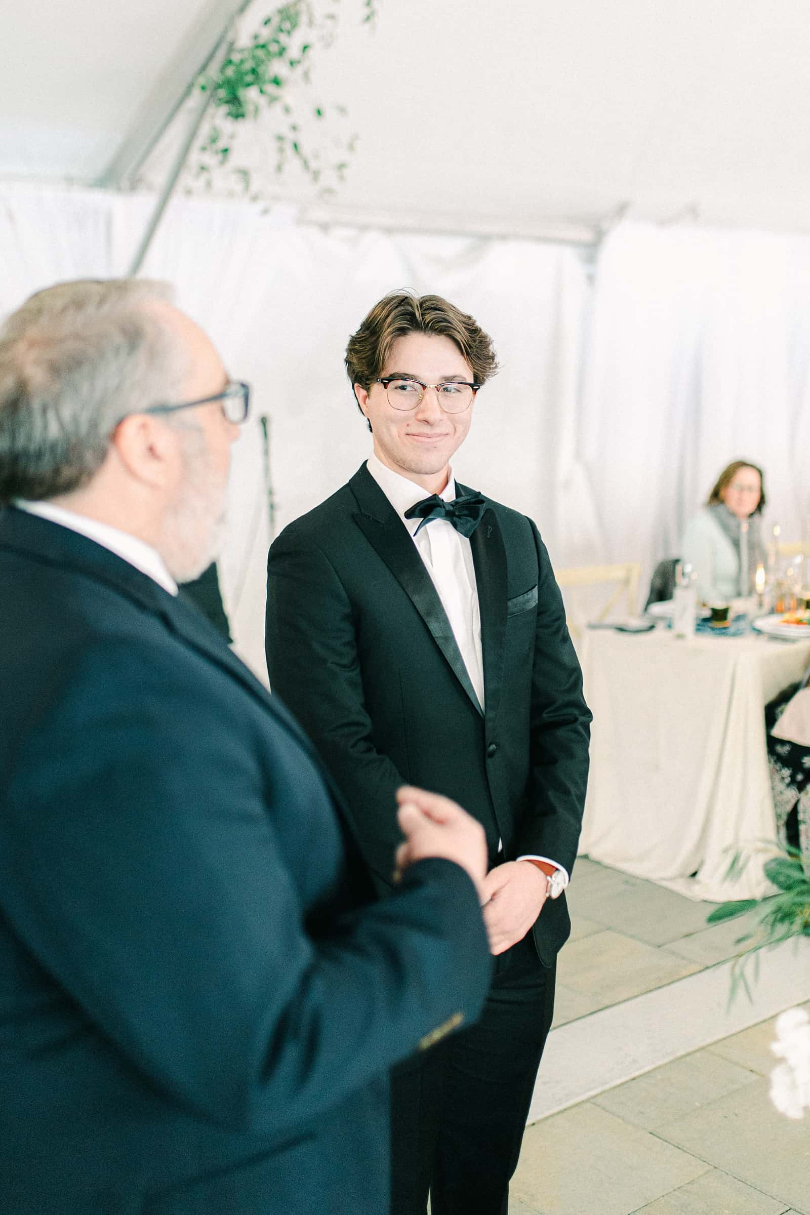 Winter wedding with white tent ceremony, groom looking at bride
