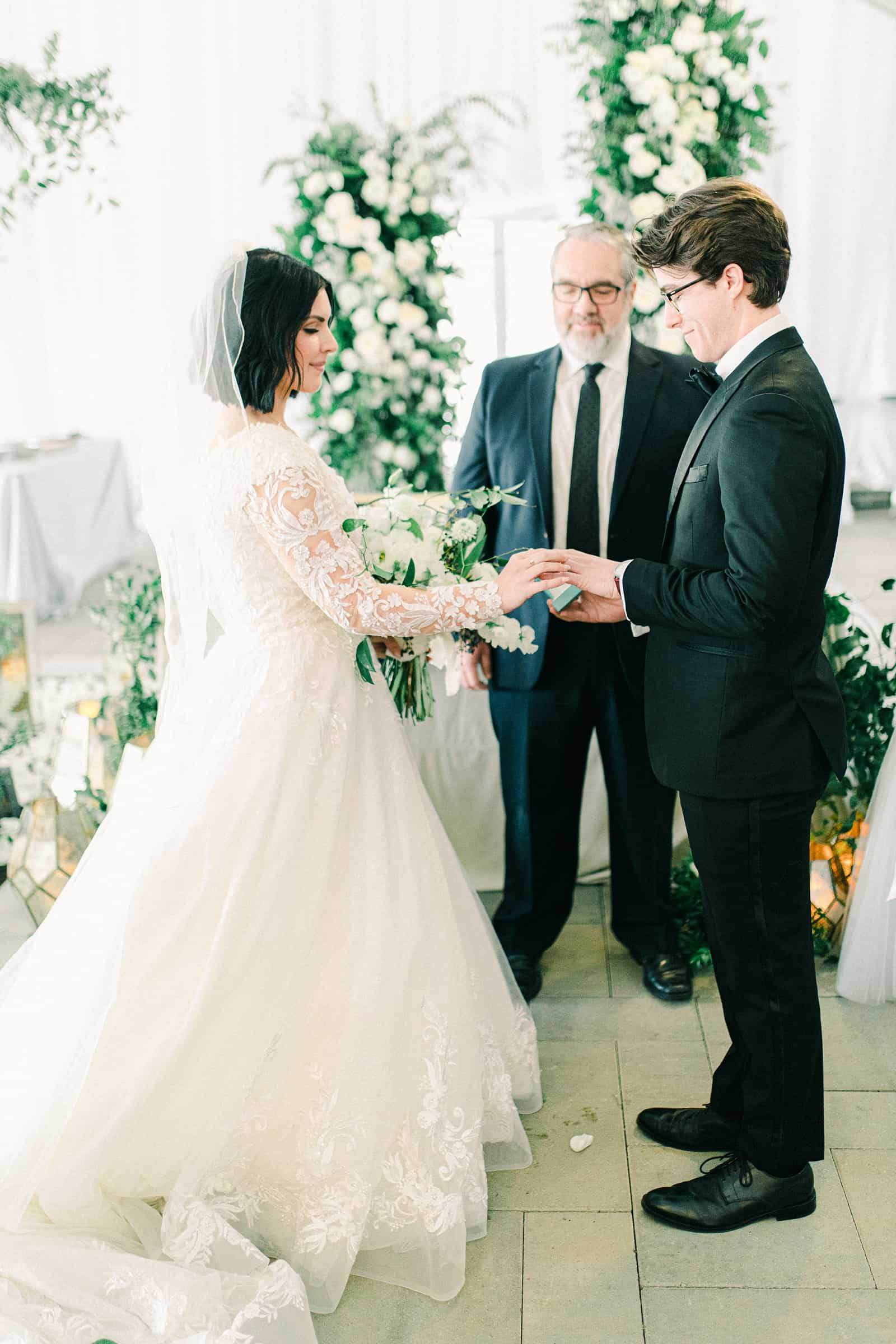Wedding ceremony in white tent, ring exchange