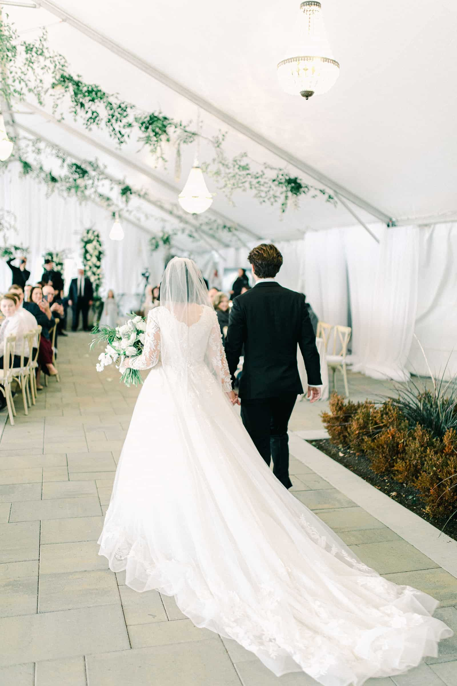 Winter wedding at Willowbridge Estate, bride and groom walk down aisle, long train