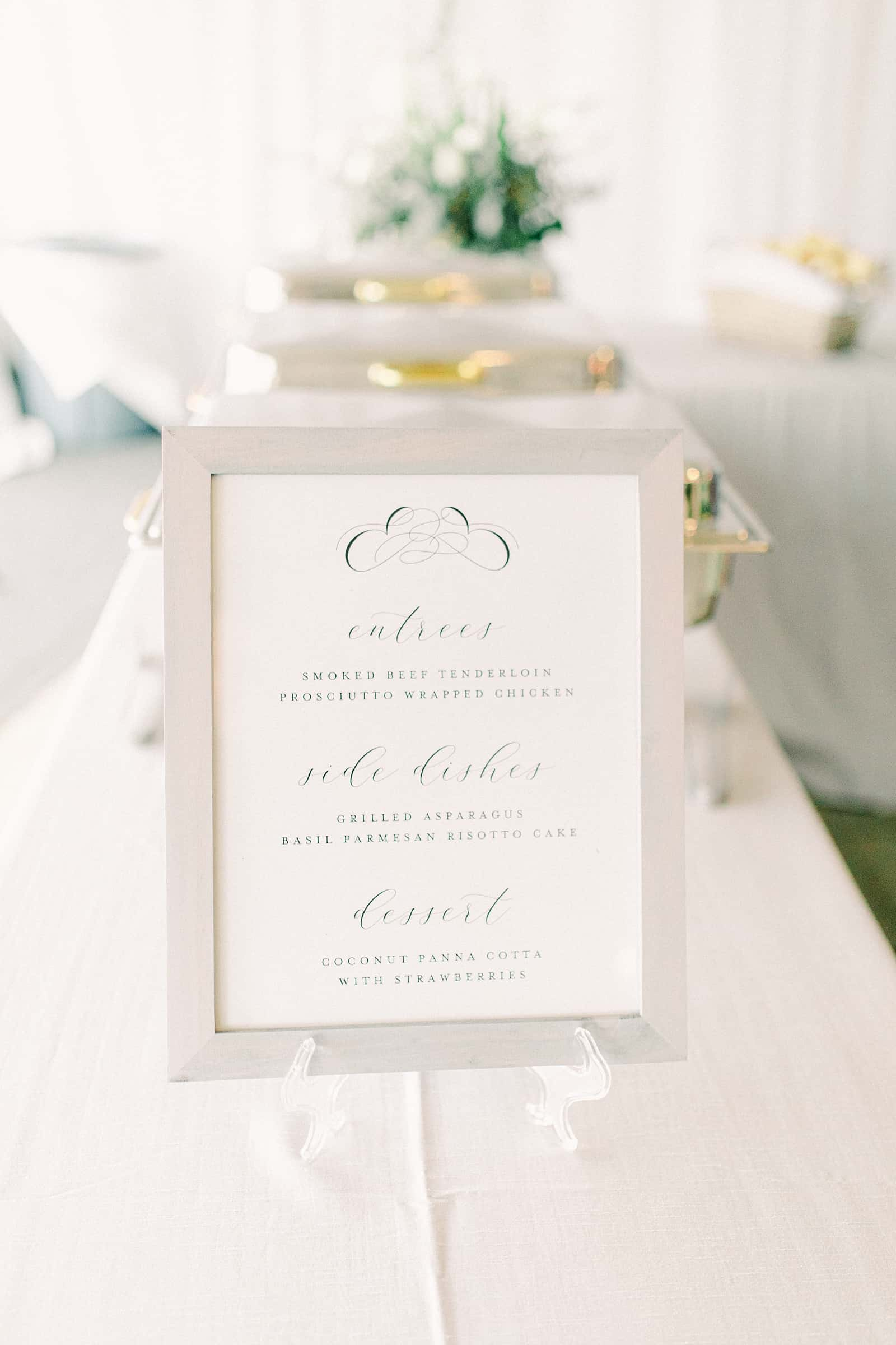 Calligraphy menu at wedding reception inside white tent