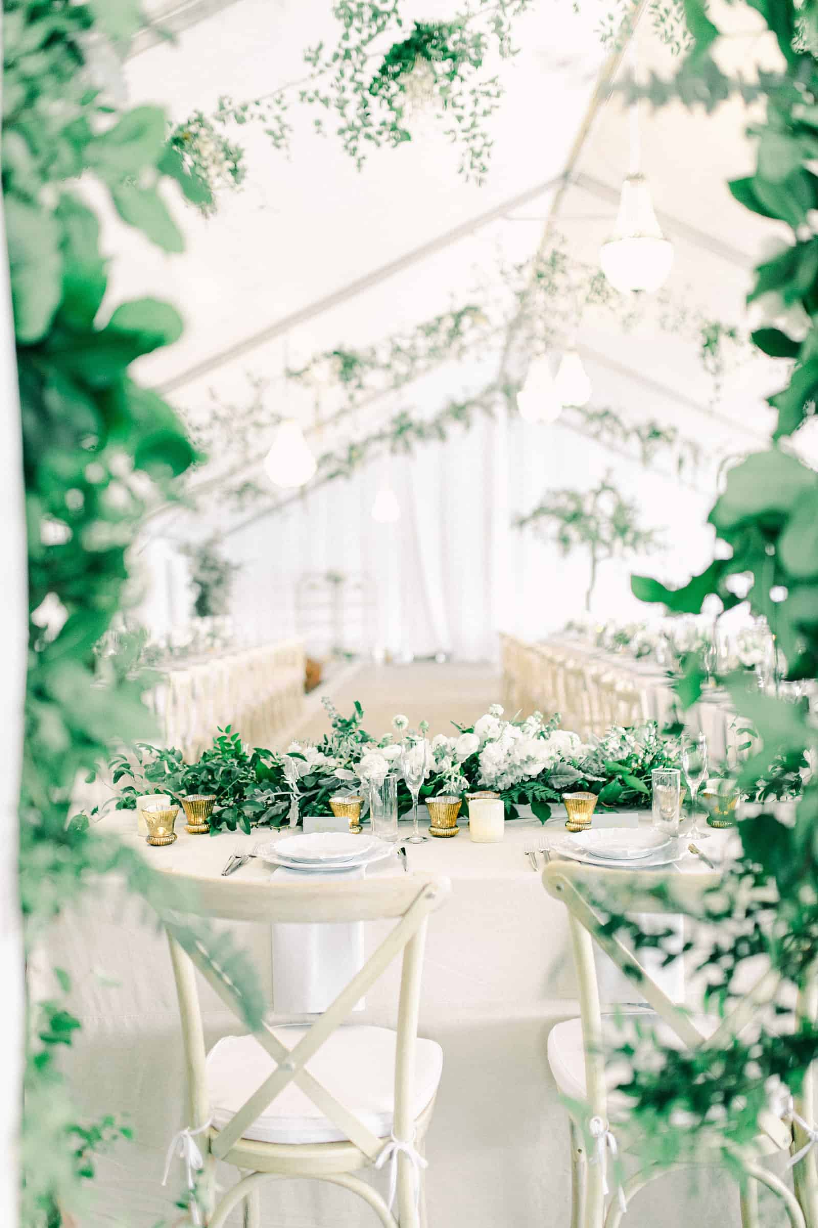 Luxury winter wedding inside white tent reception with greenery floral garland with white roses and tables with centerpieces