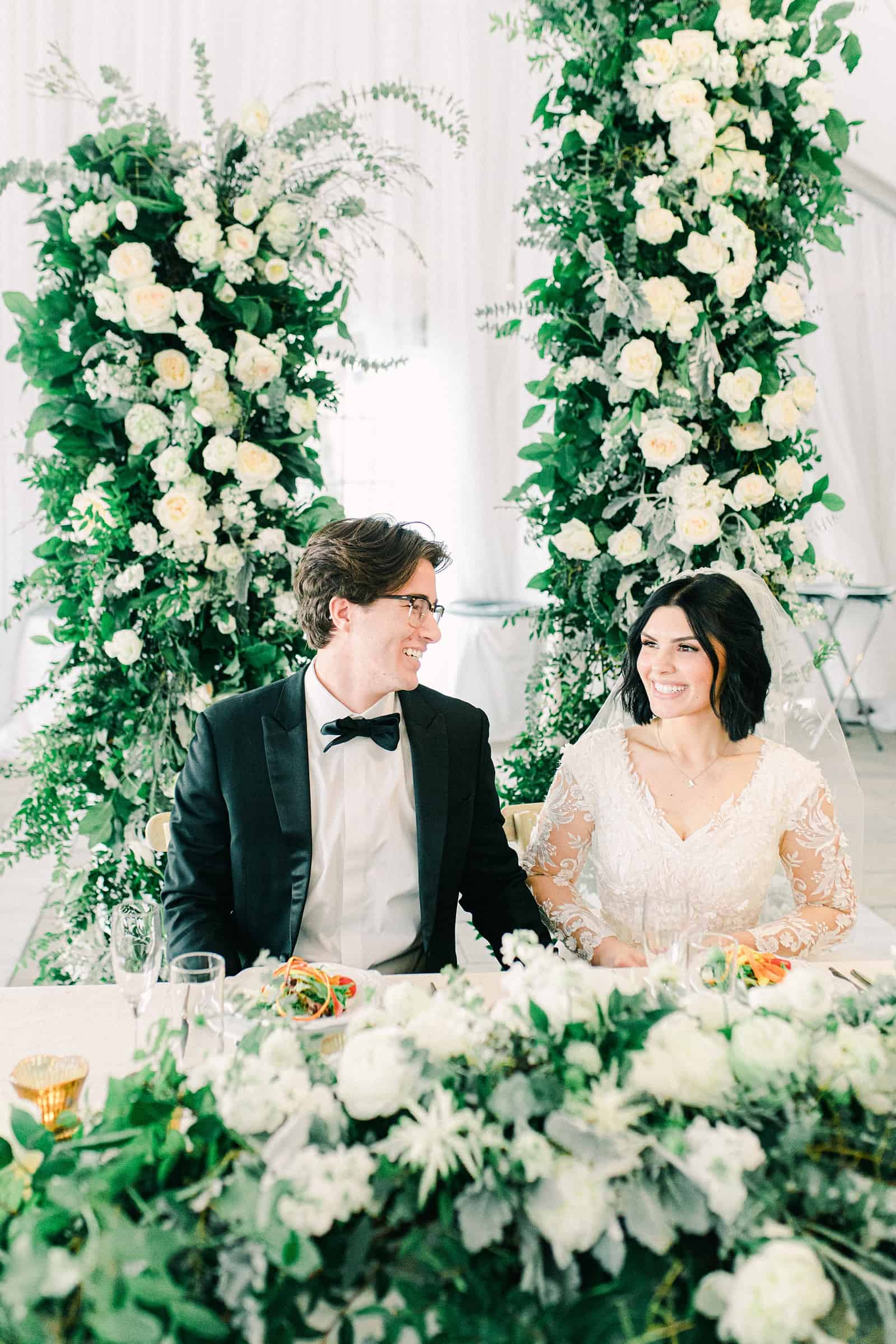 Luxury winter wedding at Willowbridge Estate in Boise, Idaho, bride and groom at sweetheart table with floral arch with white flowers and greenery backdrop