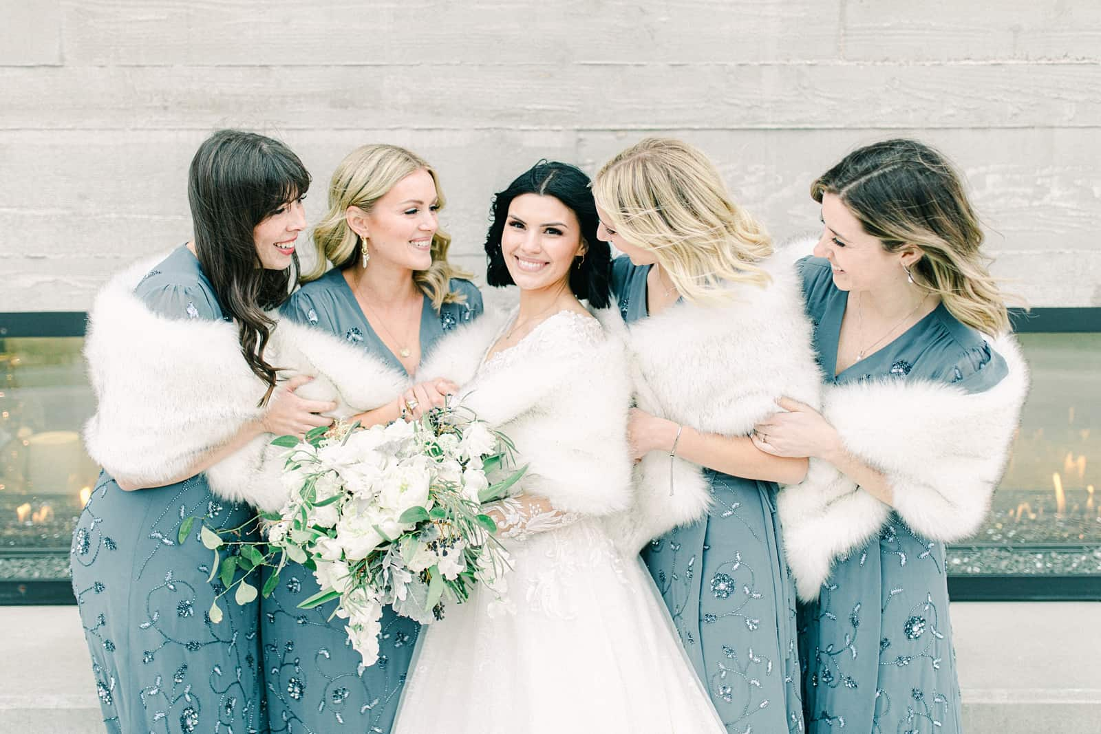 Winter wedding bride with bridesmaids, blue beaded bridesmaids dresses with white fur stoles, white flower bouquets