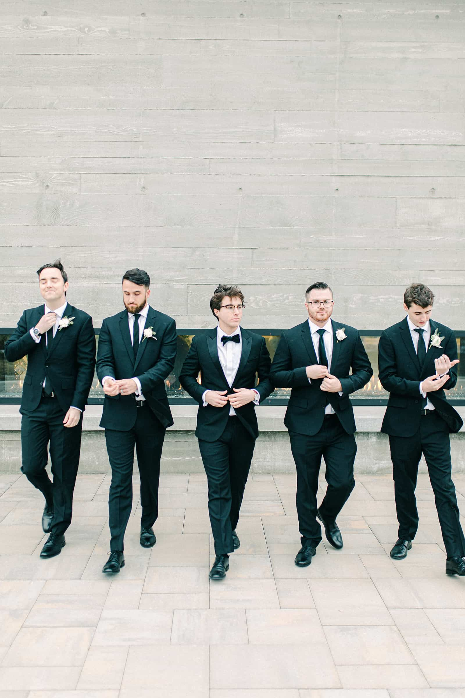 Groom and groomsmen in classic black tuxedos with bowties