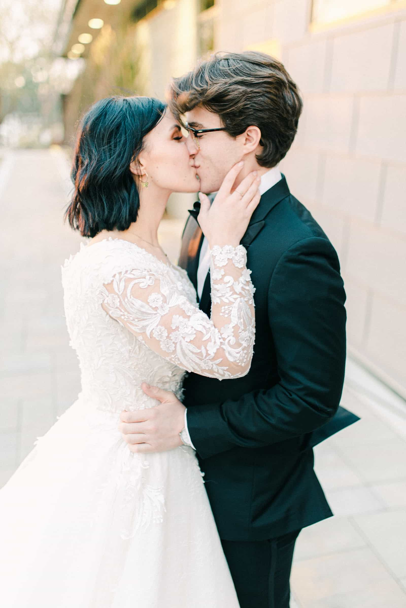 Bride and groom first kiss, lace wedding dress with long sleeves