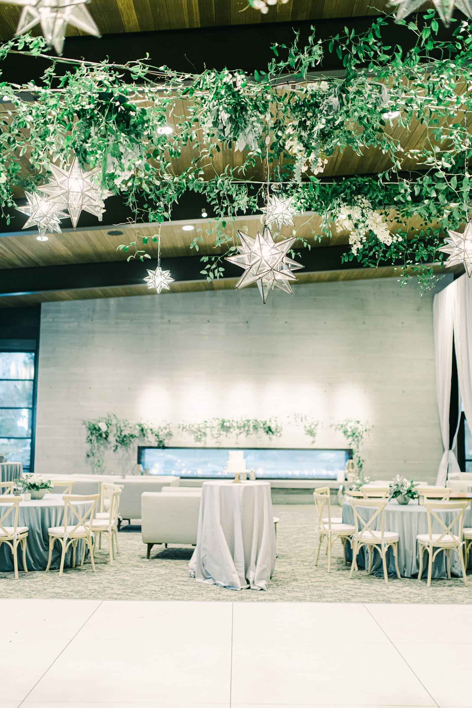 Winter wonderland wedding with star lanterns and ivy garlands, twinkle lights above dance floor