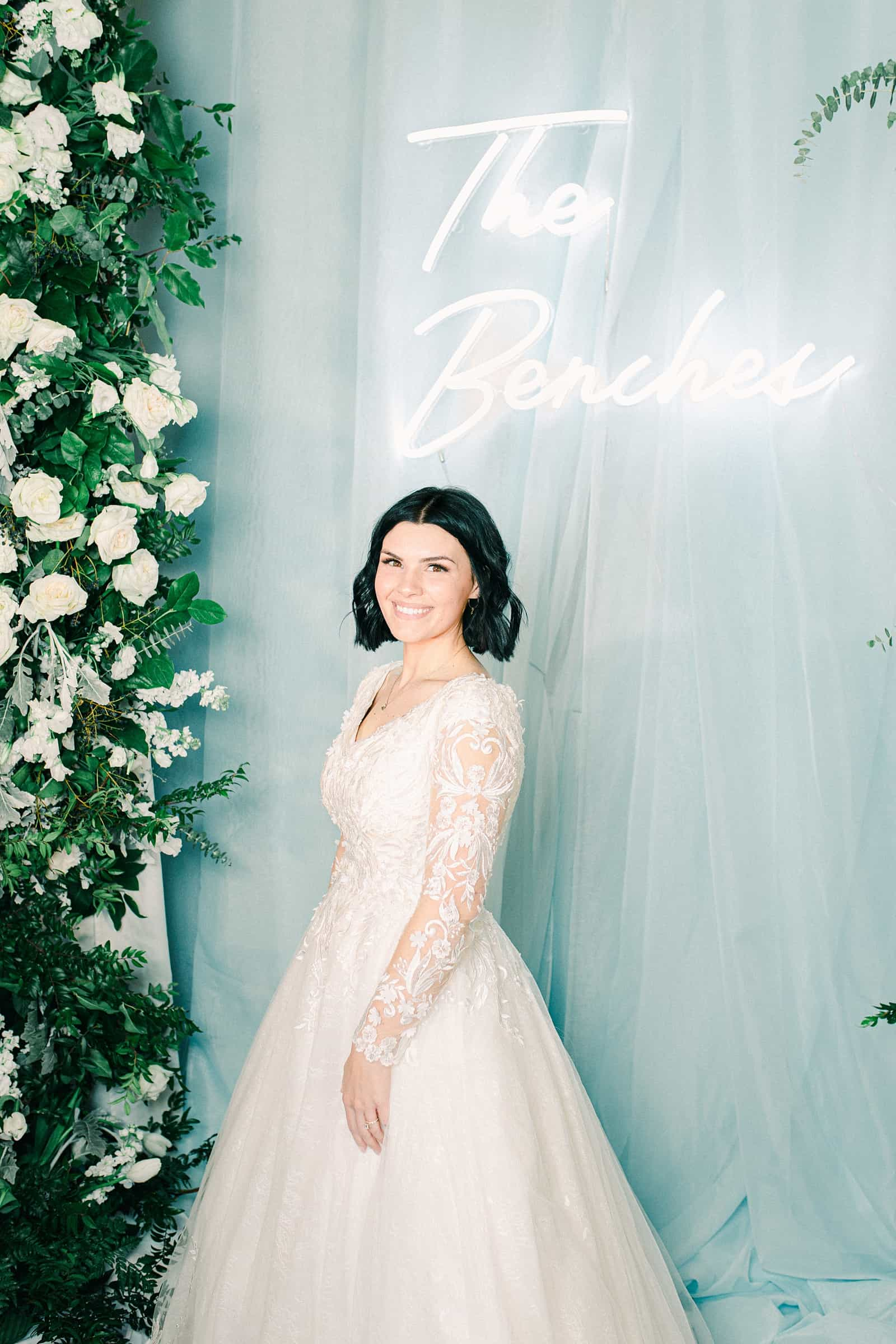 Winter wedding reception decor, bride in front of custom neon sign with last name