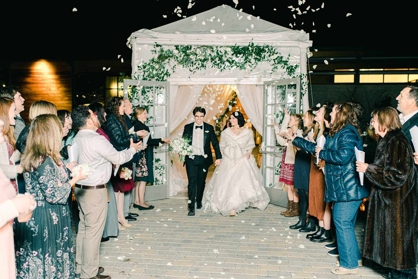 Winter wedding reception, bride and groom grand send off with rose petals