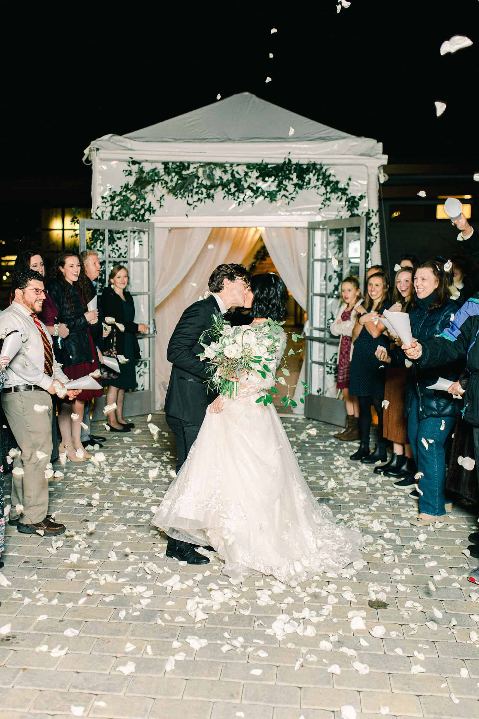 Winter wedding reception, bride and groom kiss during exit, grand send off with rose petals