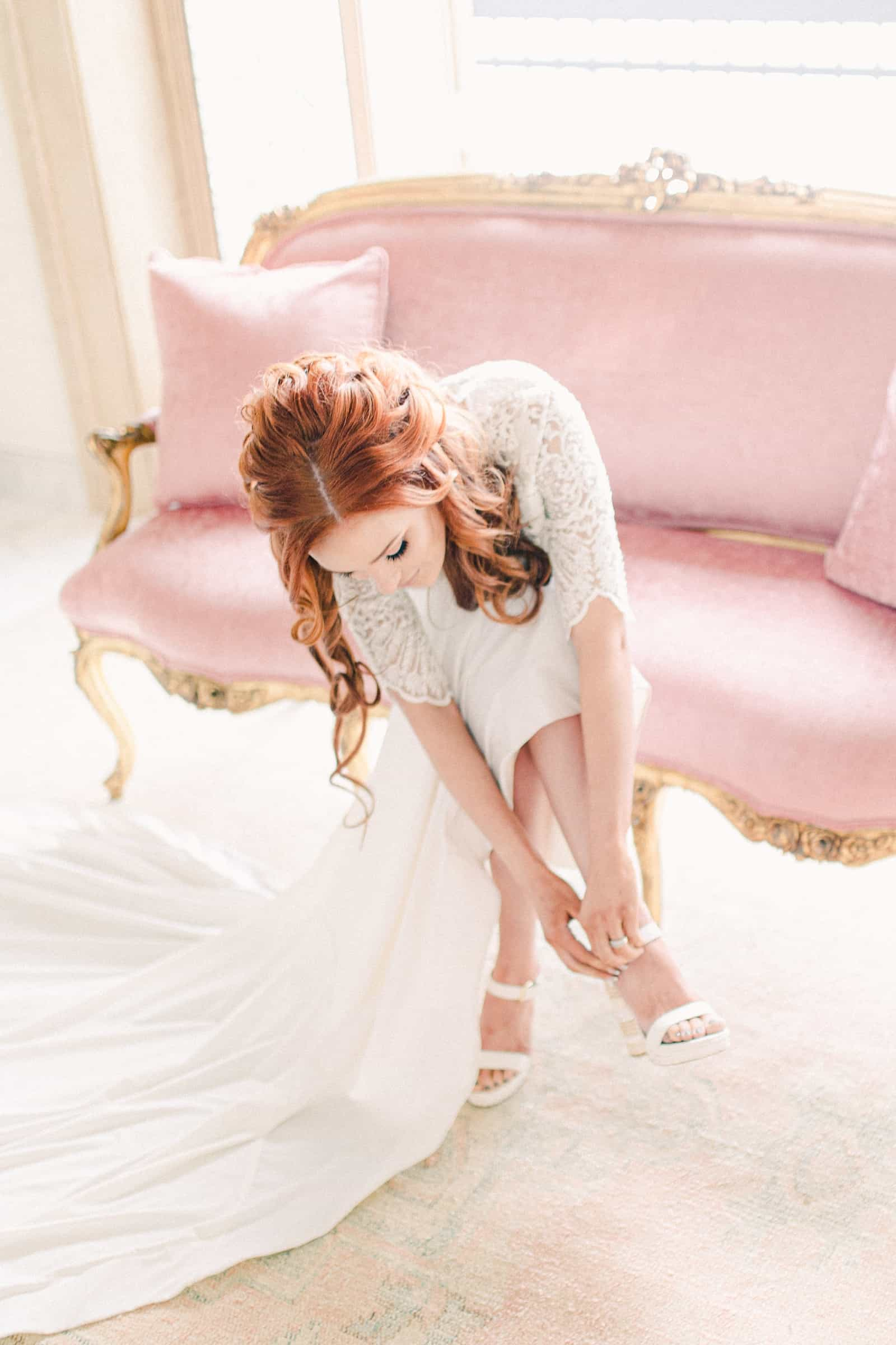 Redhead bride putting on shoes, pink couch in bride's room, bridal suite