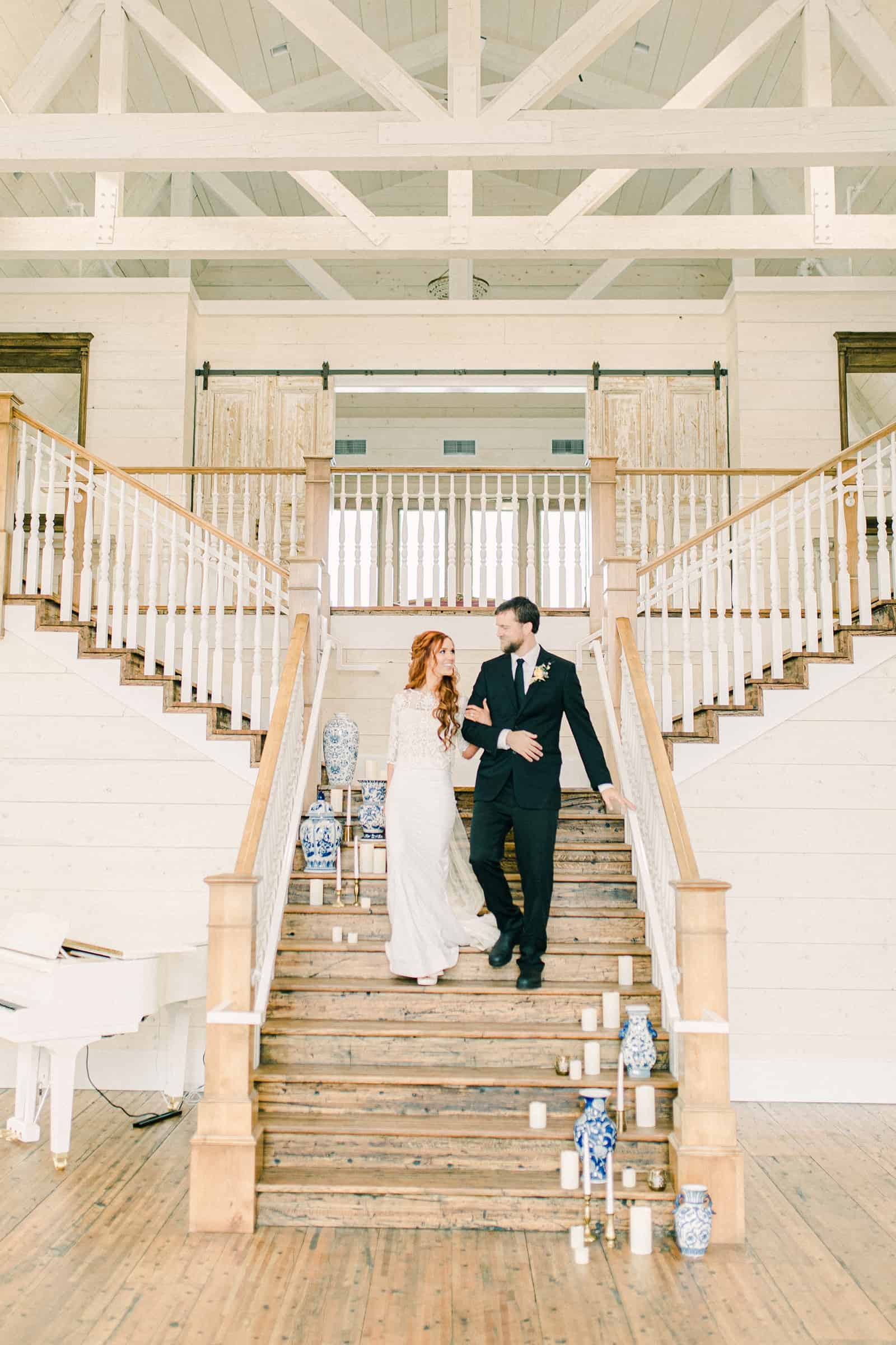 Bride and groom walk down staircase at Walker Farms, Utah white barn modern wedding venue