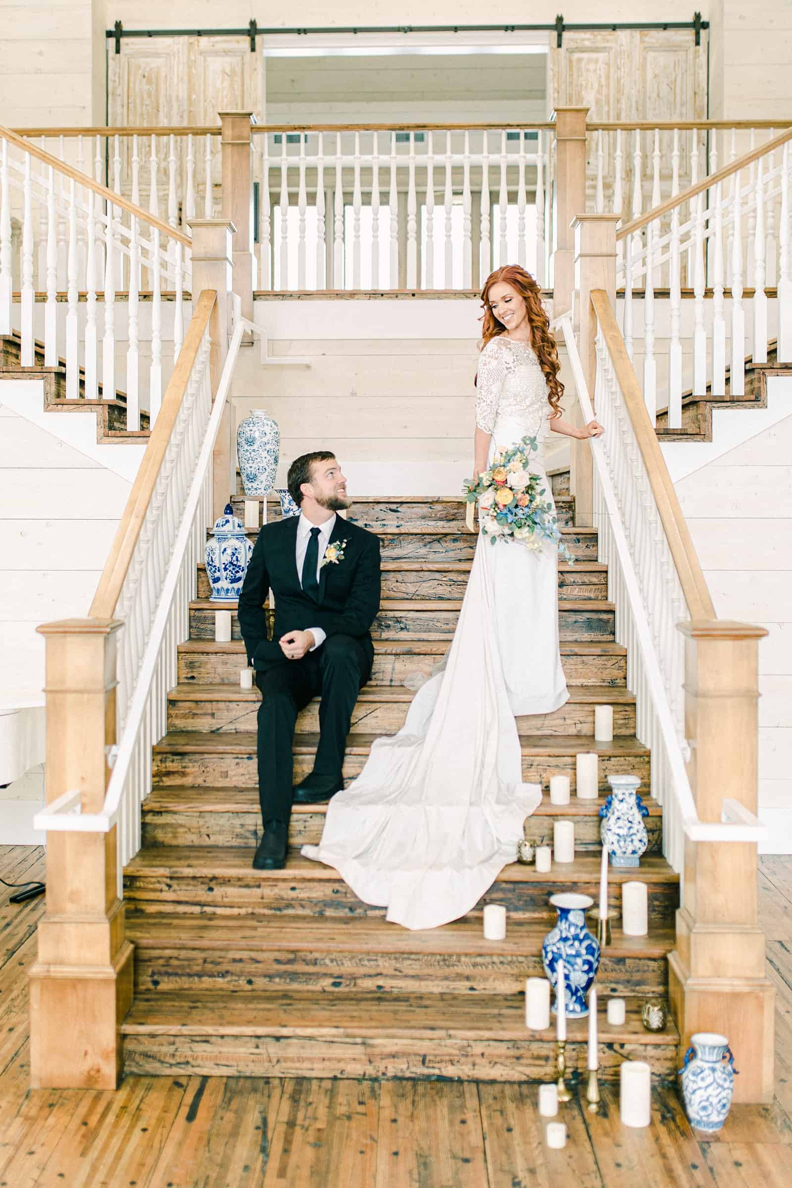 Bride and groom on staircase with vases and candles