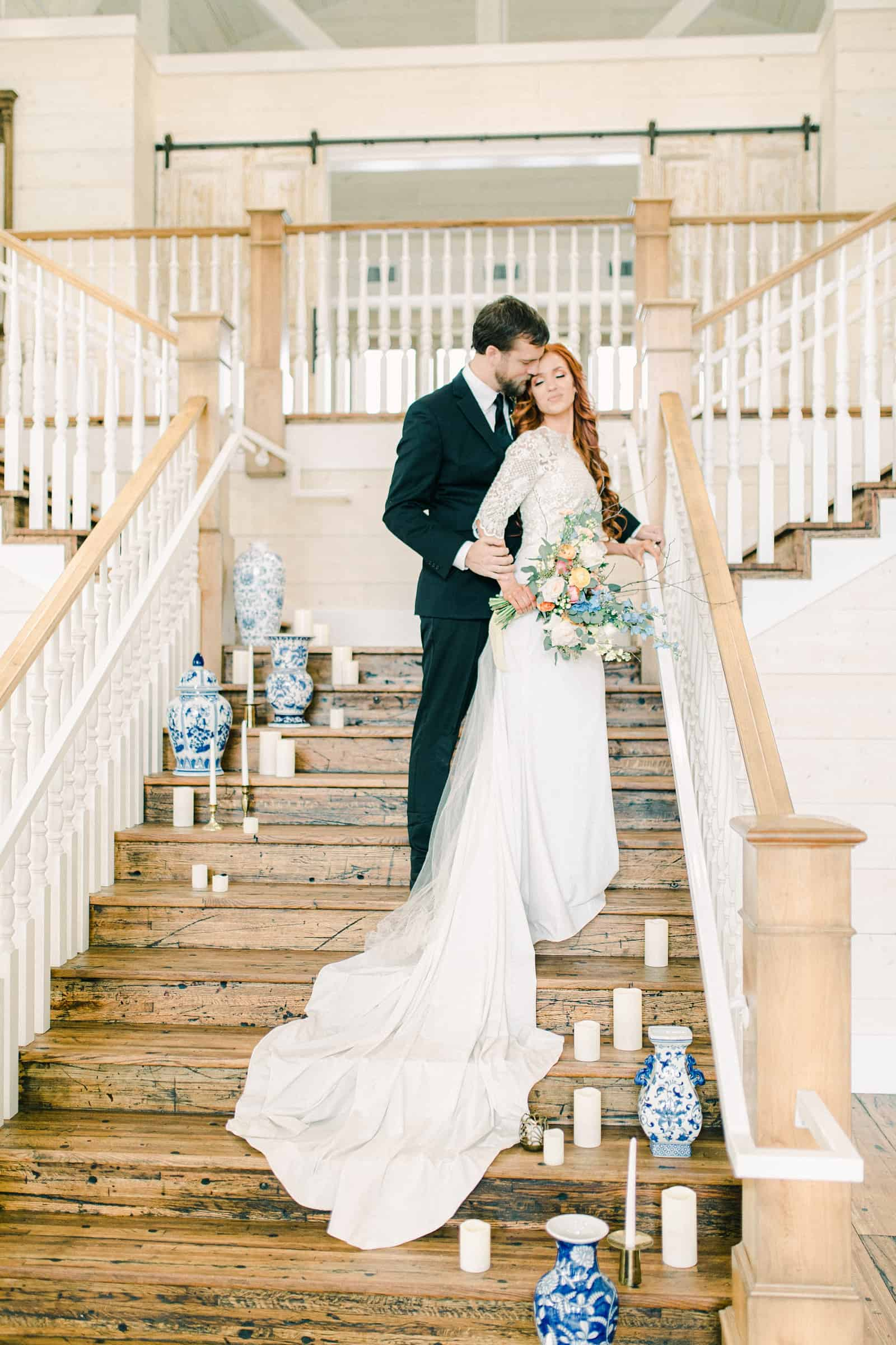 Bride and groom on staircase with vases and candles, Utah County wedding venue