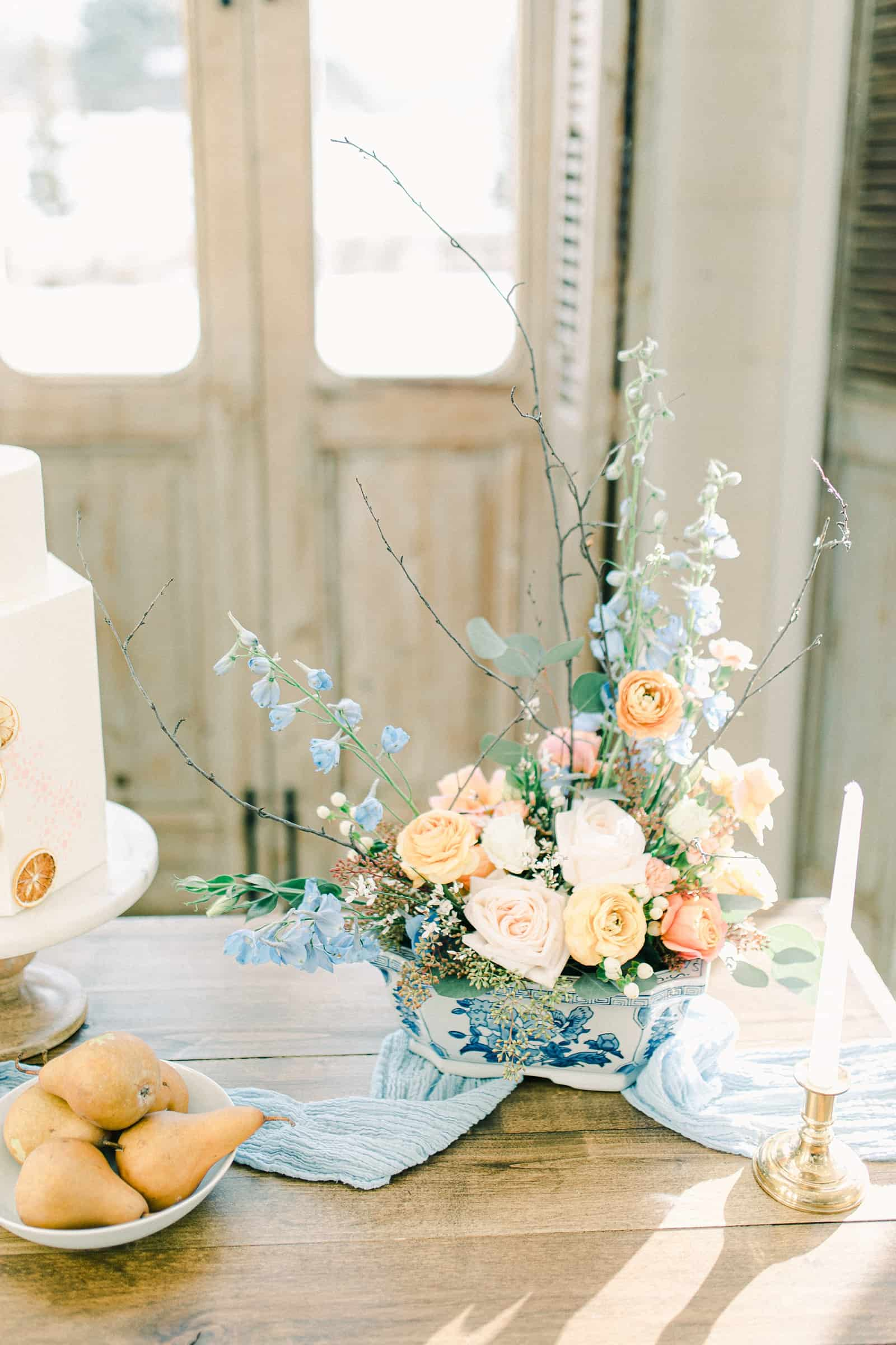Wedding flowers, florist centerpiece, pastel wedding colors, light blue table runner, white buttercream wedding cake