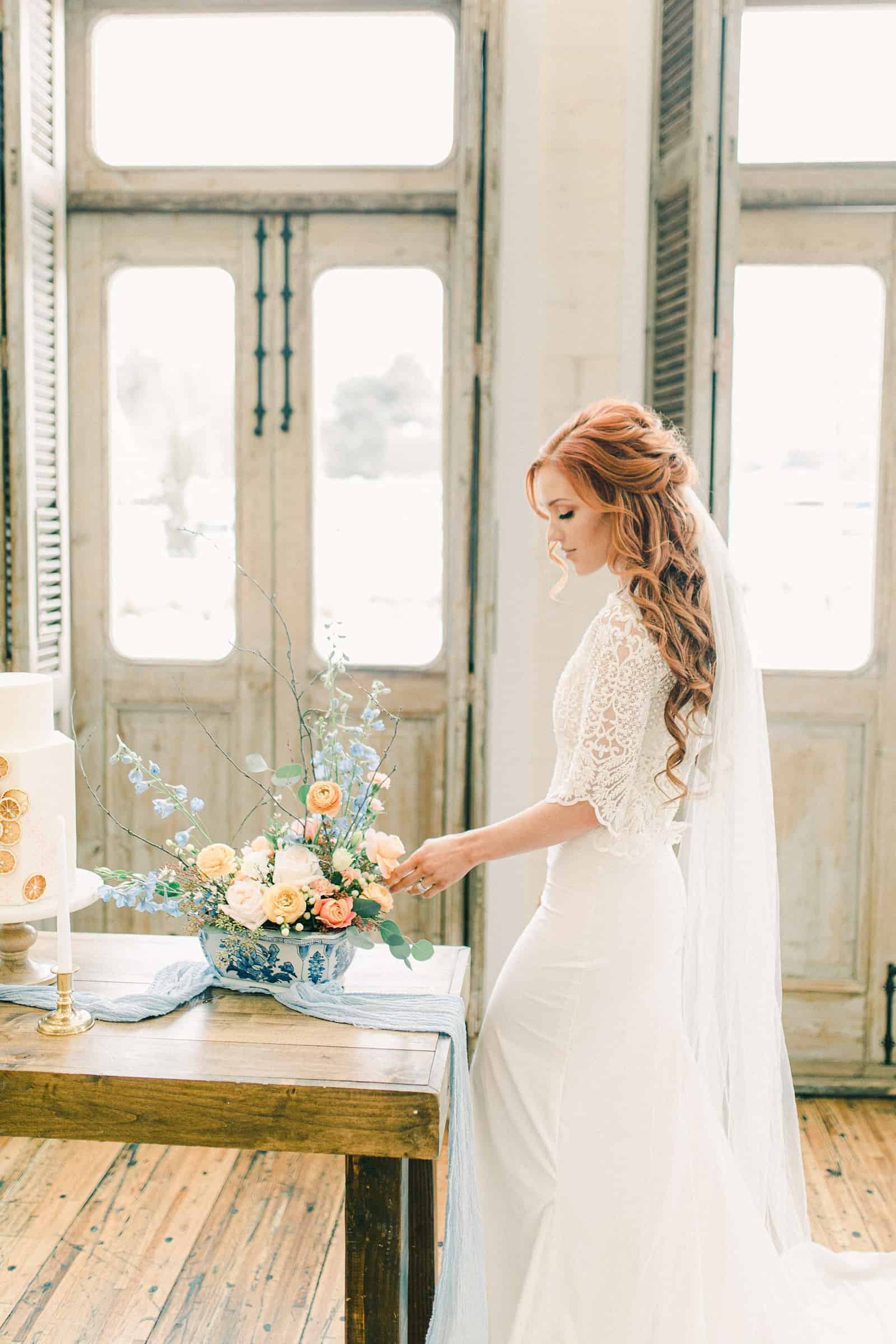 Bride with red hair wearing three quarter length sleeve lace wedding dress and veil, pastel wedding colors, spring wedding centerpiece and small simple wedding cake with oranges