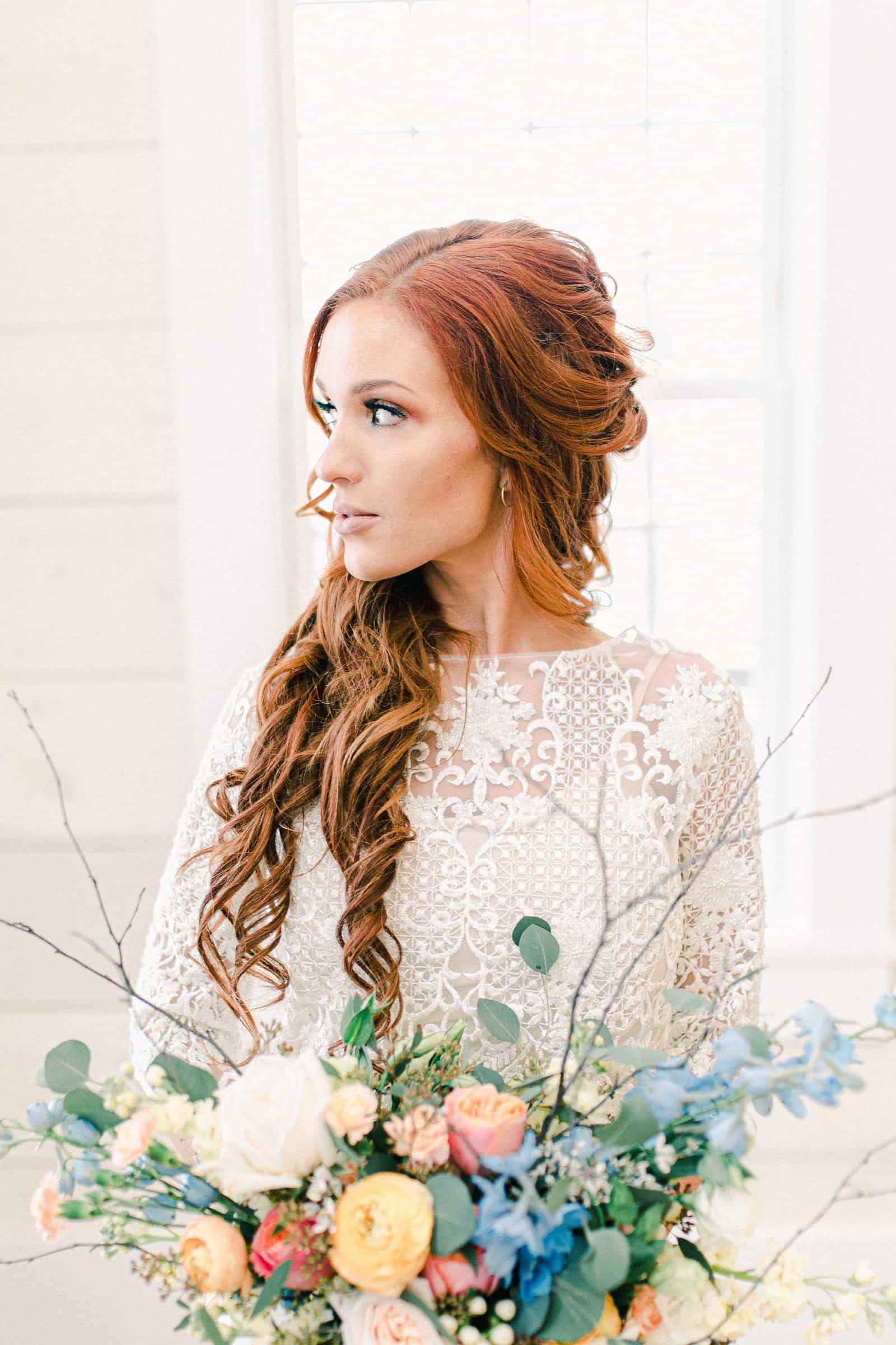 Bride with long lace sleeves holding wedding bouquet with pastel colors, blue, pink, orange, peach flowers, long curly wedding hairstyle redhead, Freckled Fox