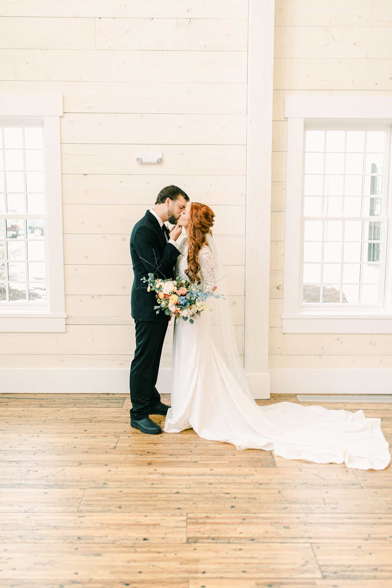 Bride and groom first kiss, white barn wedding venue