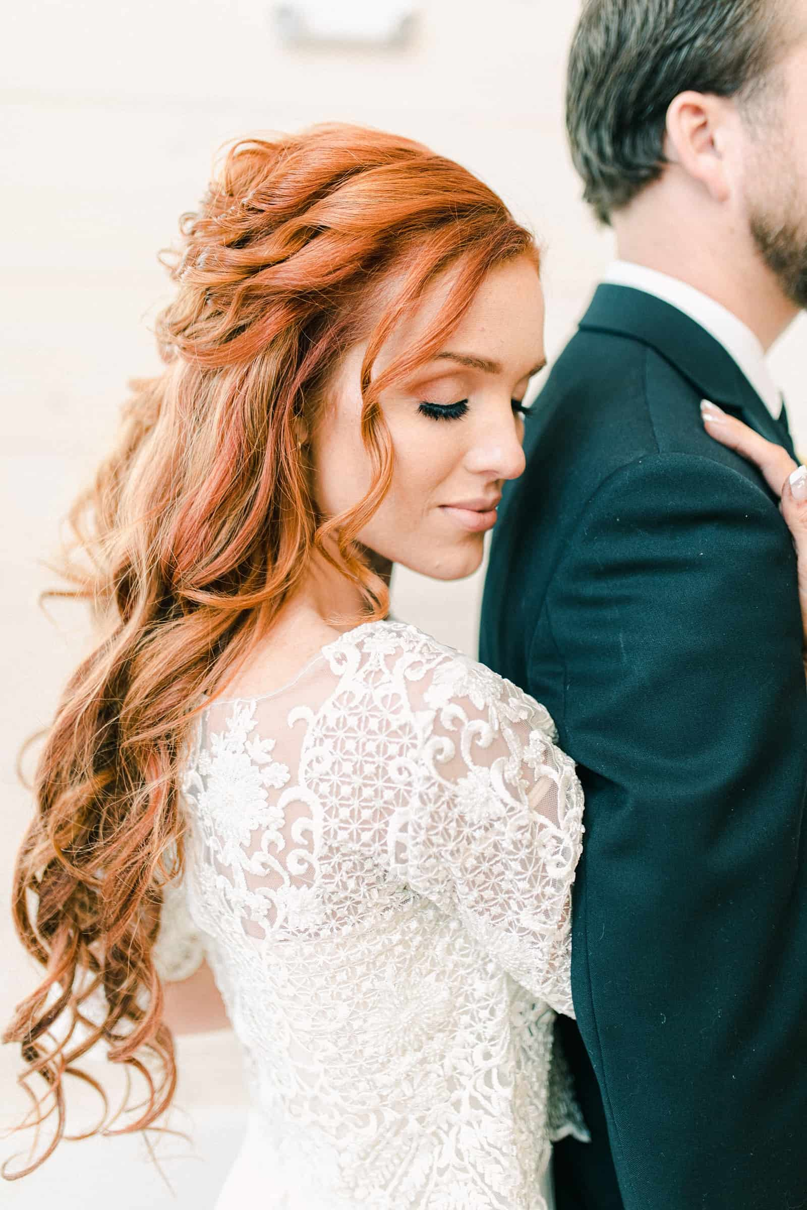 Redhead bride with wedding dress with long lace sleeves, long half up wedding hairstyle, boho bride