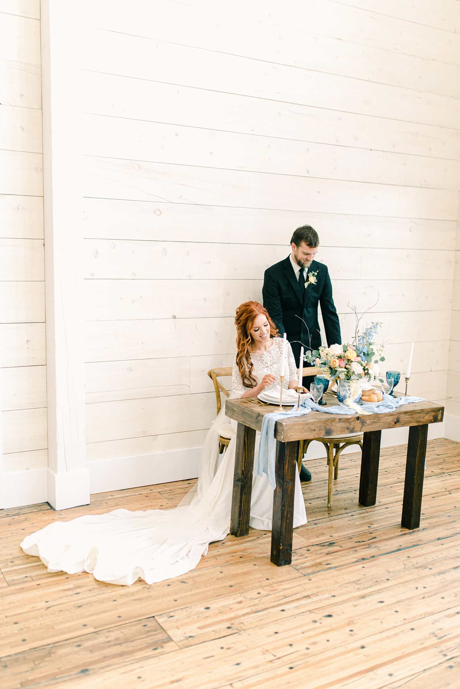 Bride and groom sit at wedding reception table, white shiplap walls, white barn wedding venue