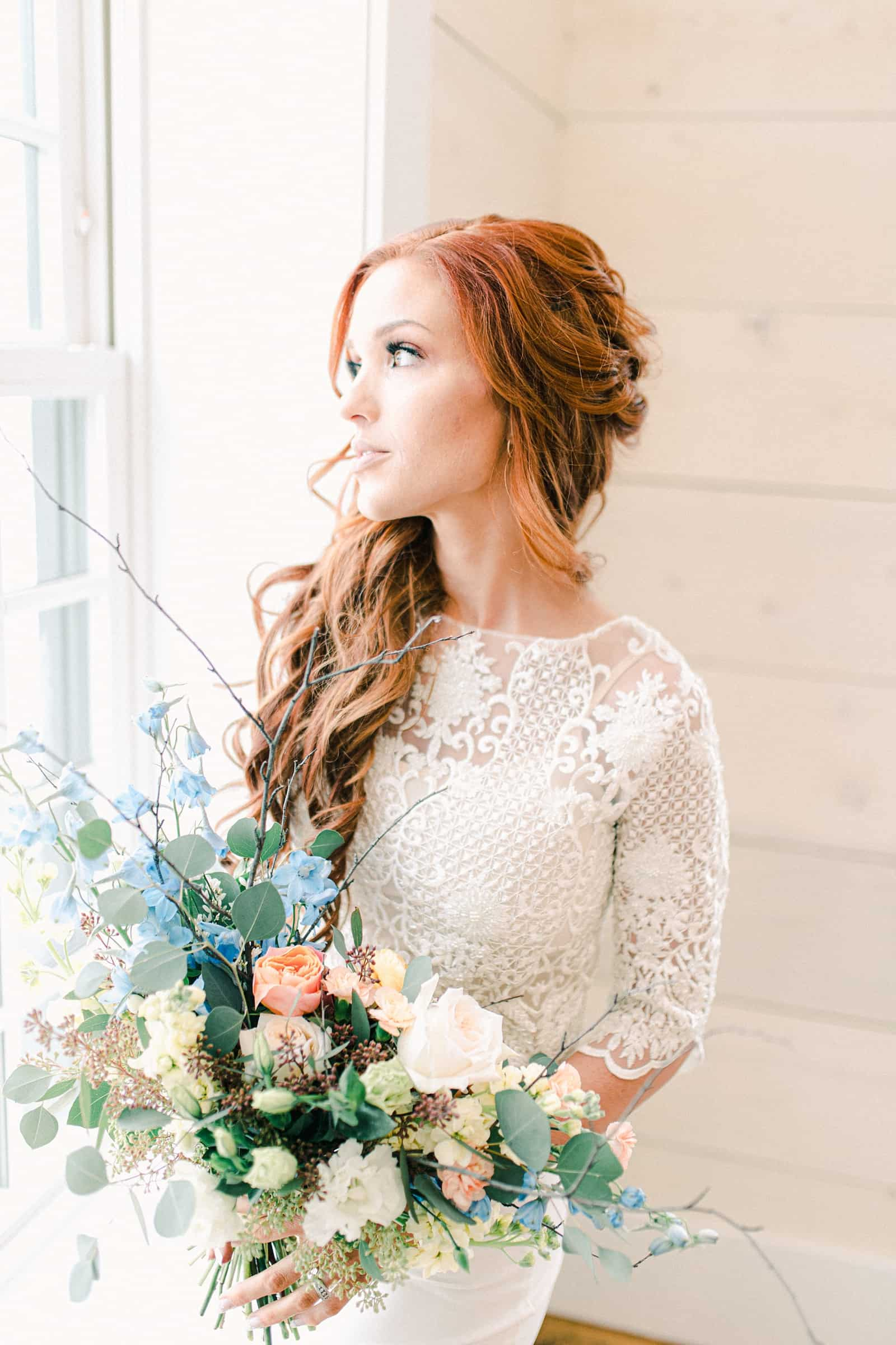 Bride with long lace sleeves looks out window holding wedding bouquet with pastel colors, blue, pink, orange, peach flowers