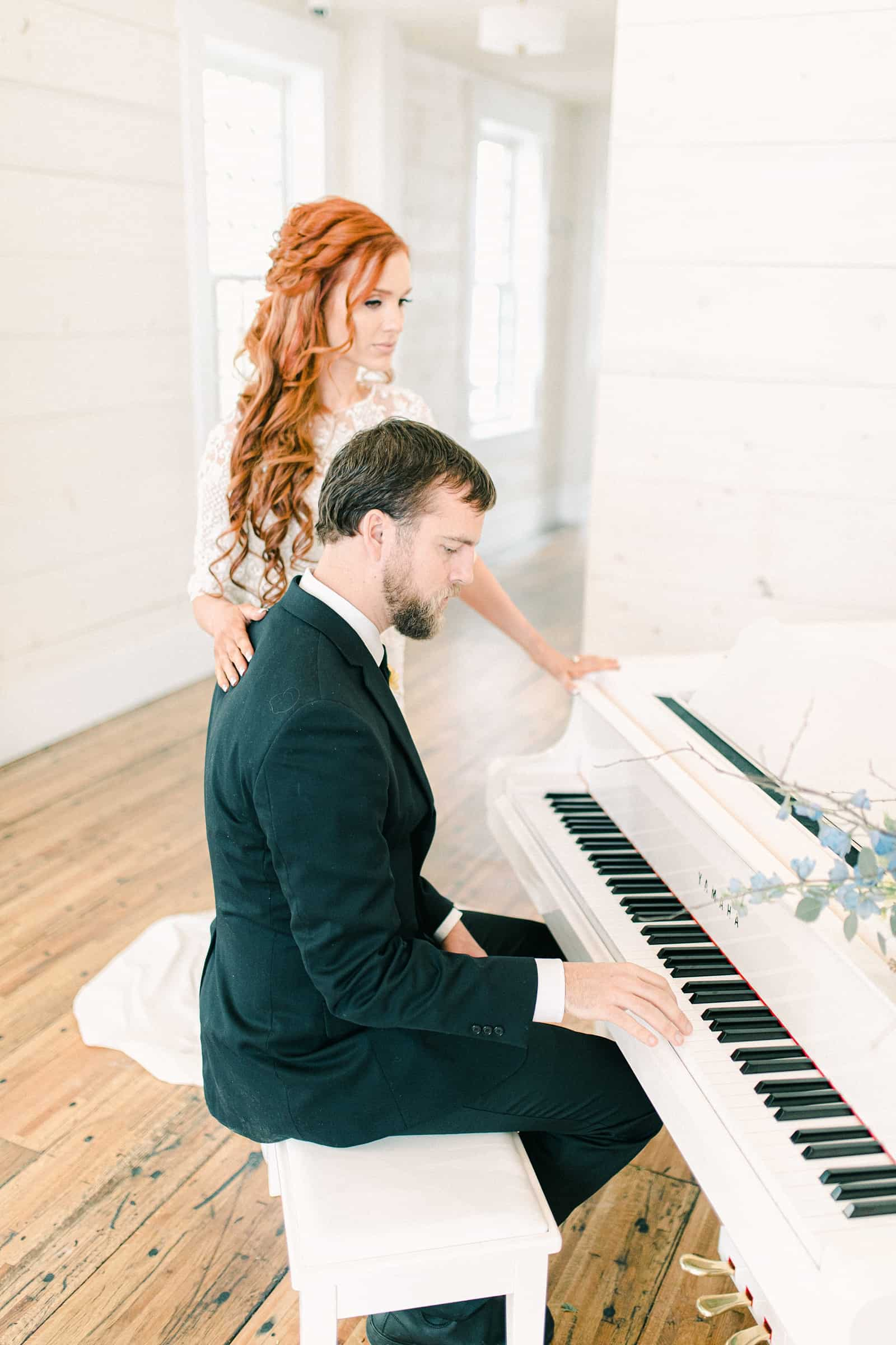 Groom plays white baby grand piano for bride on their wedding day