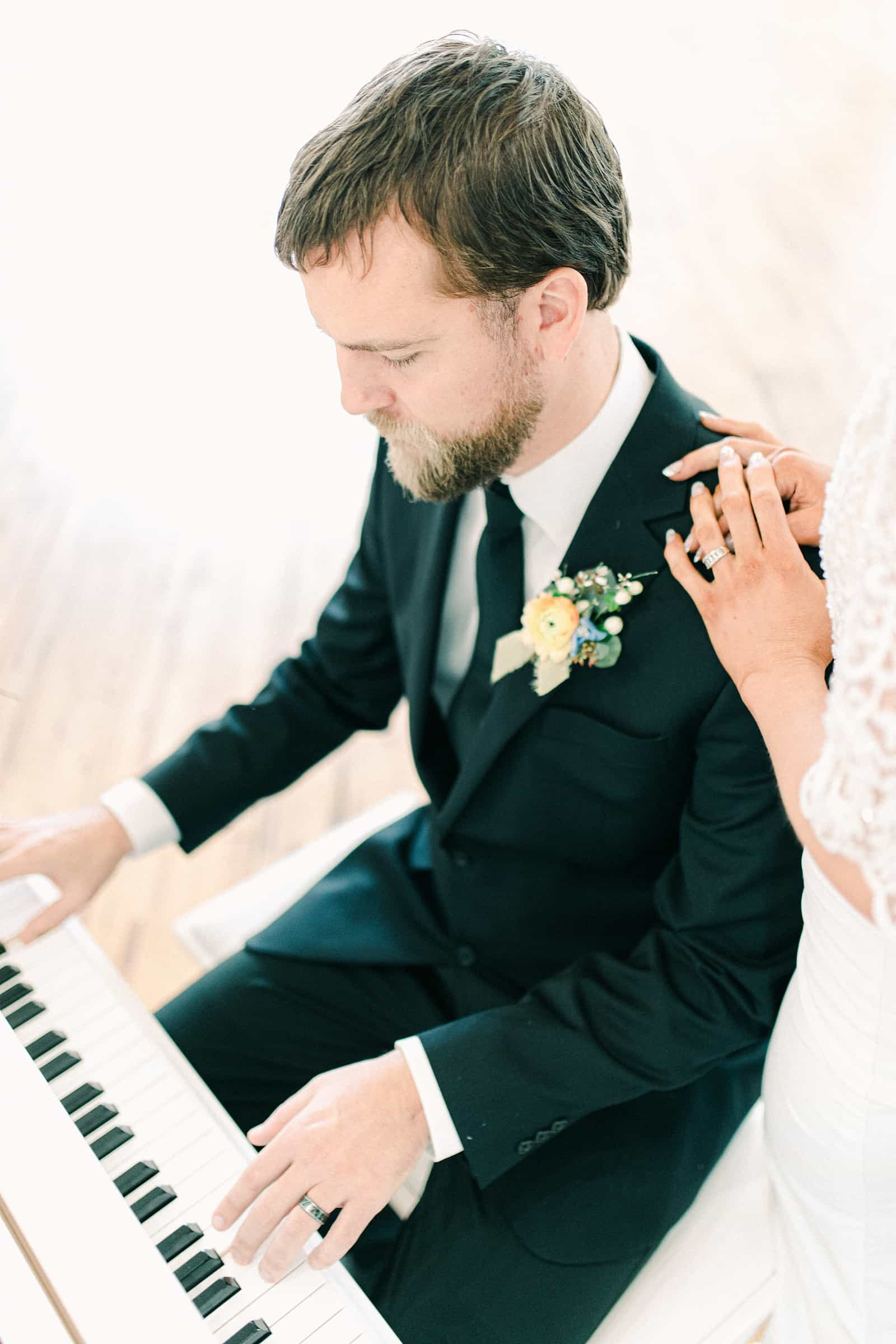 Groom plays white baby grand piano for bride on their wedding day, groom in classic black suit with black tie